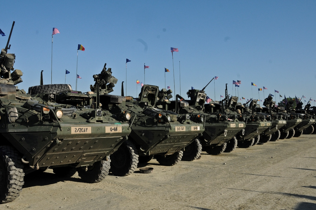 Troopers assigned to 2nd Squadron, 2nd Cavalry Regiment, place American, Romanian and NATO flags on their Stryker Combat Vehicles in preparation for the unit's Cavalry March to the Cincu Training Center, at Mihail Kogalniceanu Air Base, Romania, May 13, 2015. This event will not only focus on transporting troopers and their equipment to a new Romanian training facility, but it will also give the unit a chance to interact with the local populace while improving on relations with their host nation in support of Operation Atlantic Resolve-South. (U.S. Army photo by Sgt. William A. Tanner/released)