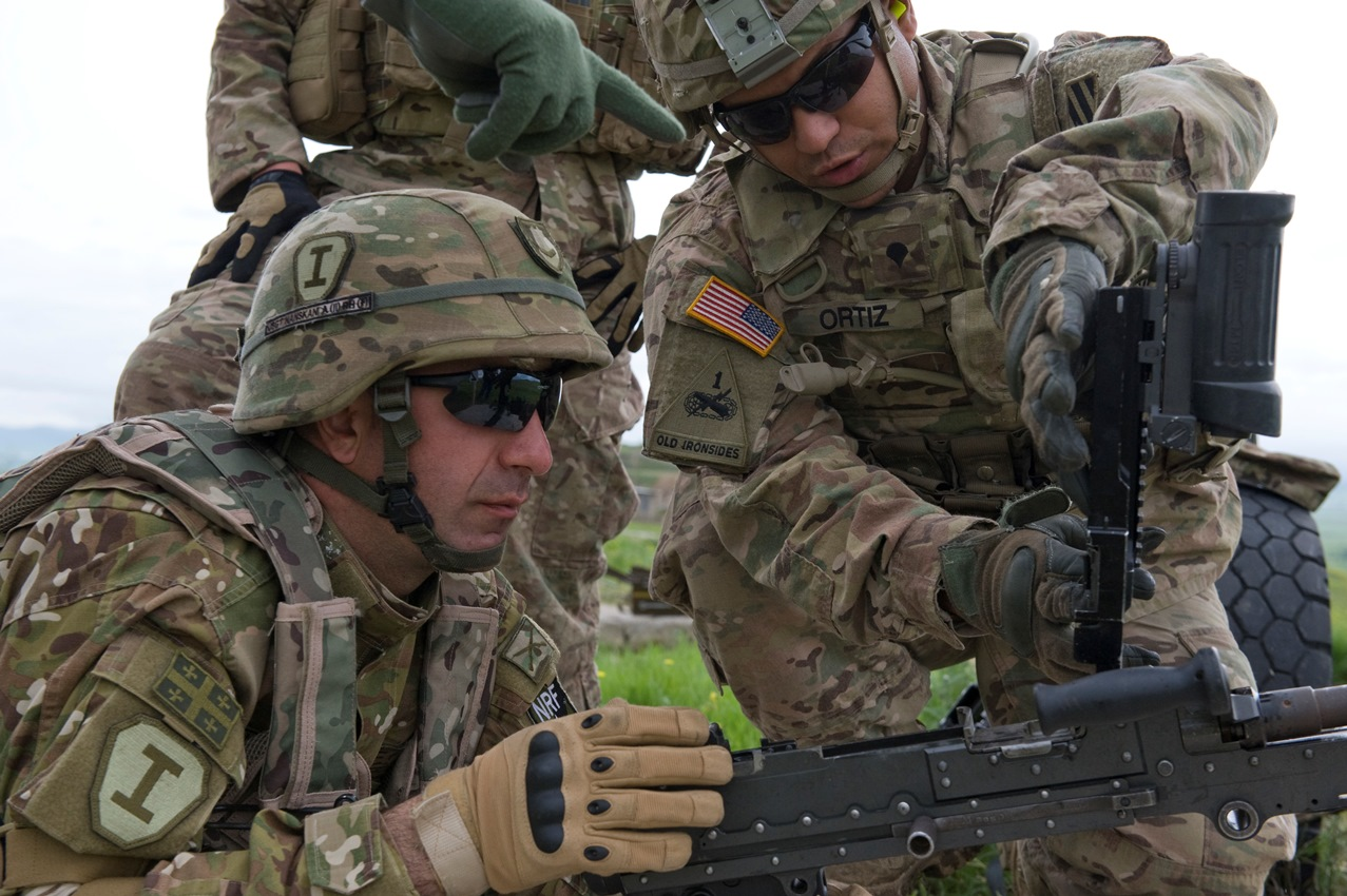 Spc. Ramon Ortiz, an infantryman assigned to Company A, 2nd Battalion, 7th Infantry Regiment, 1st Brigade, 3rd Infantry Division, trains a Georgian soldier on how to clear empty shell rounds from the loading tray of a M240B during clearing procedures May 14, 2015. Noble Partner is a field training and live-fire exercise between the U.S. Army and the Georgian military to support Georgia's participation in the NATO Response Force and build military ties between the two nations. (U.S. Army Photo by Sgt. Daniel Cole, Army Europe Public Affairs)