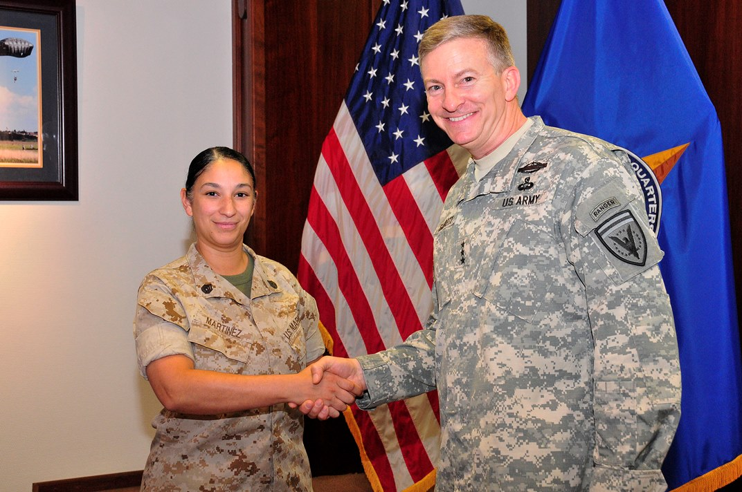U.S. European Command Deputy Commander Lt. Gen. William Garrett III presents a coin to SSgt Luz Martinez, Executive Assistant, for exceptional duty performance.
