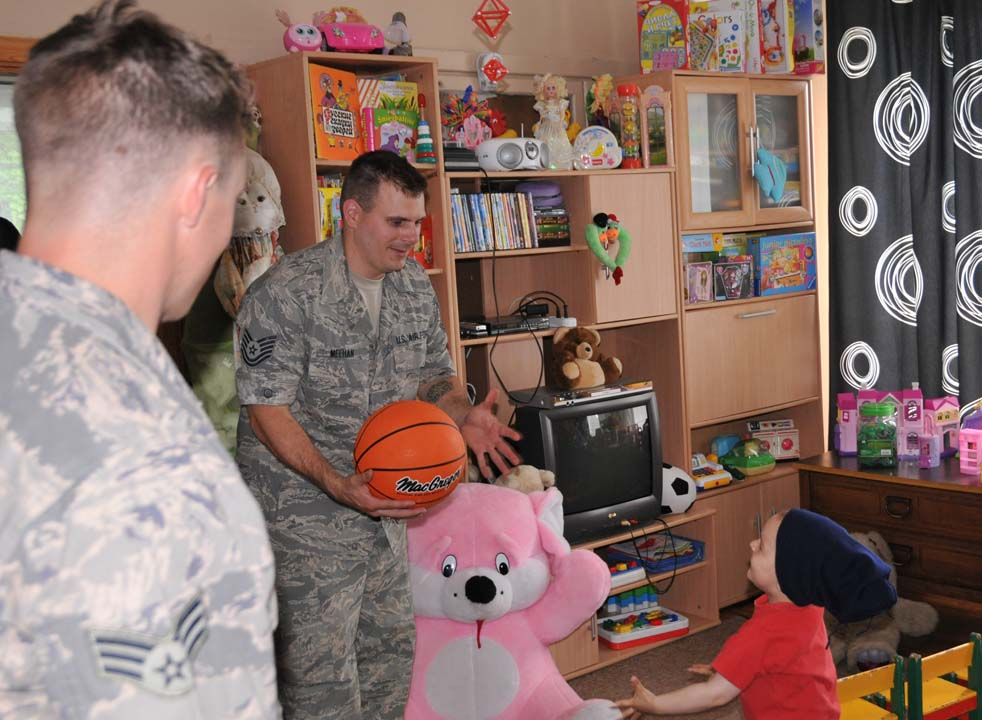 Technical Sergeant Joseph Meehan plays with a child while visiting the Najuene Orphanage. Meehan is a member of the 171st Air Refueling Wing Civil Engineer Squadron working on a Humanitarian Civic Assistance project in Latvia.