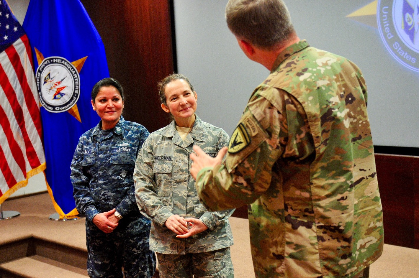 U.S. European Command Deputy Commander Lt. Gen. William Garrett III presents a coin to PO1 Riva Ali, left, and Master Sgt. Alicia Singerman, Secretary of the Joint Staff, for their outstanding duty performance.