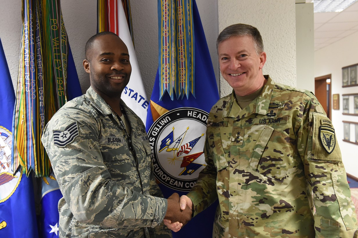 U.S. European Command Deputy Commander Lt. Gen. W. Burke Garrett III presents a coin to Tech. Sgt. Dwayne Blandin, Emergency Actions Controller, for outstanding duty performance Apr. 15, 2016.