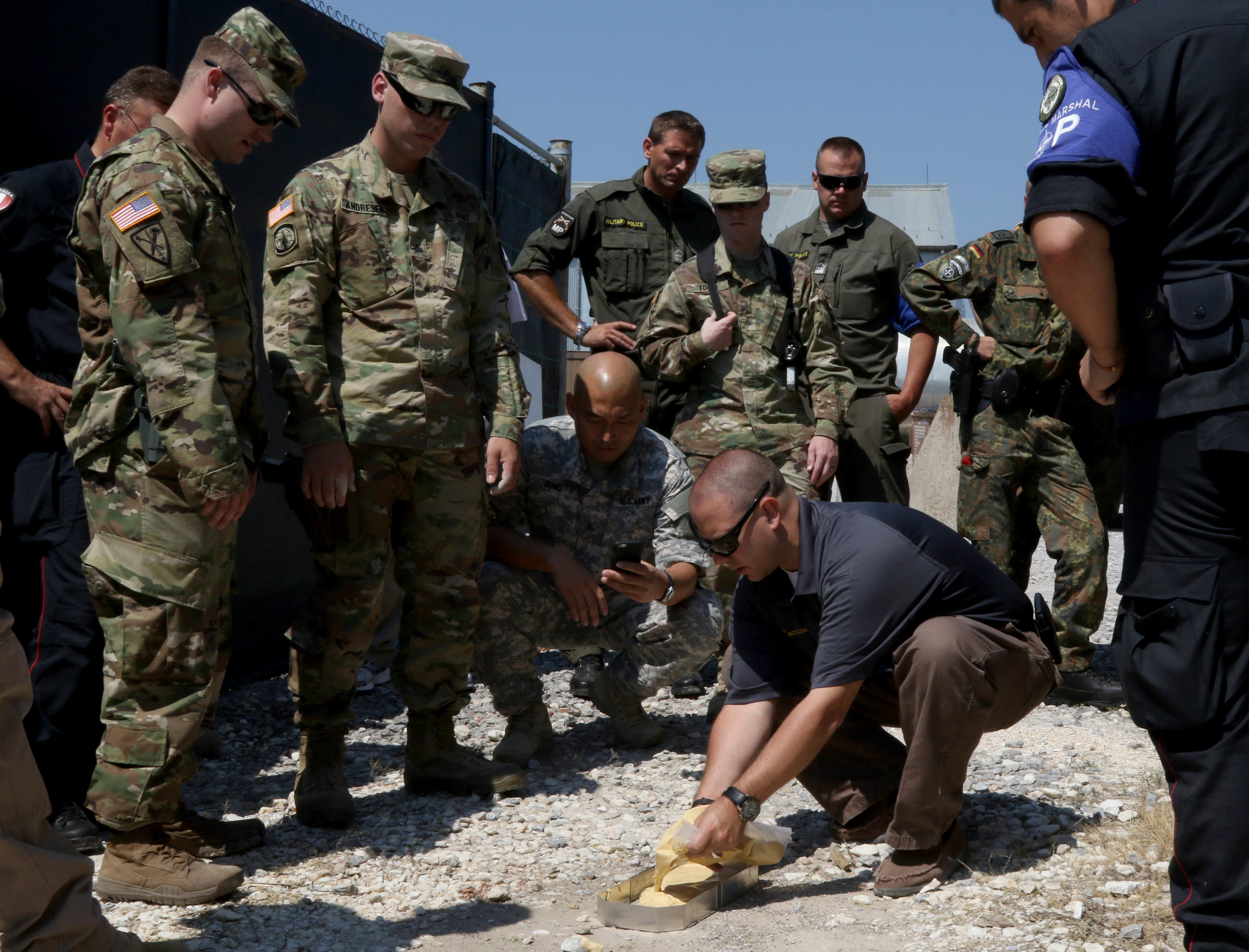 A criminal investigation special agent, from U.S. Army Europe, shows how to properly cast a foot impression to service members from NATO's Kosovo Force during a Crime Scene Investigation course held on Camp Bondsteel, Kosovo, July 13, 2016. (U.S. Army photo by: Staff Sgt. Thomas Duval, Multinational Battle Group-East public affairs)