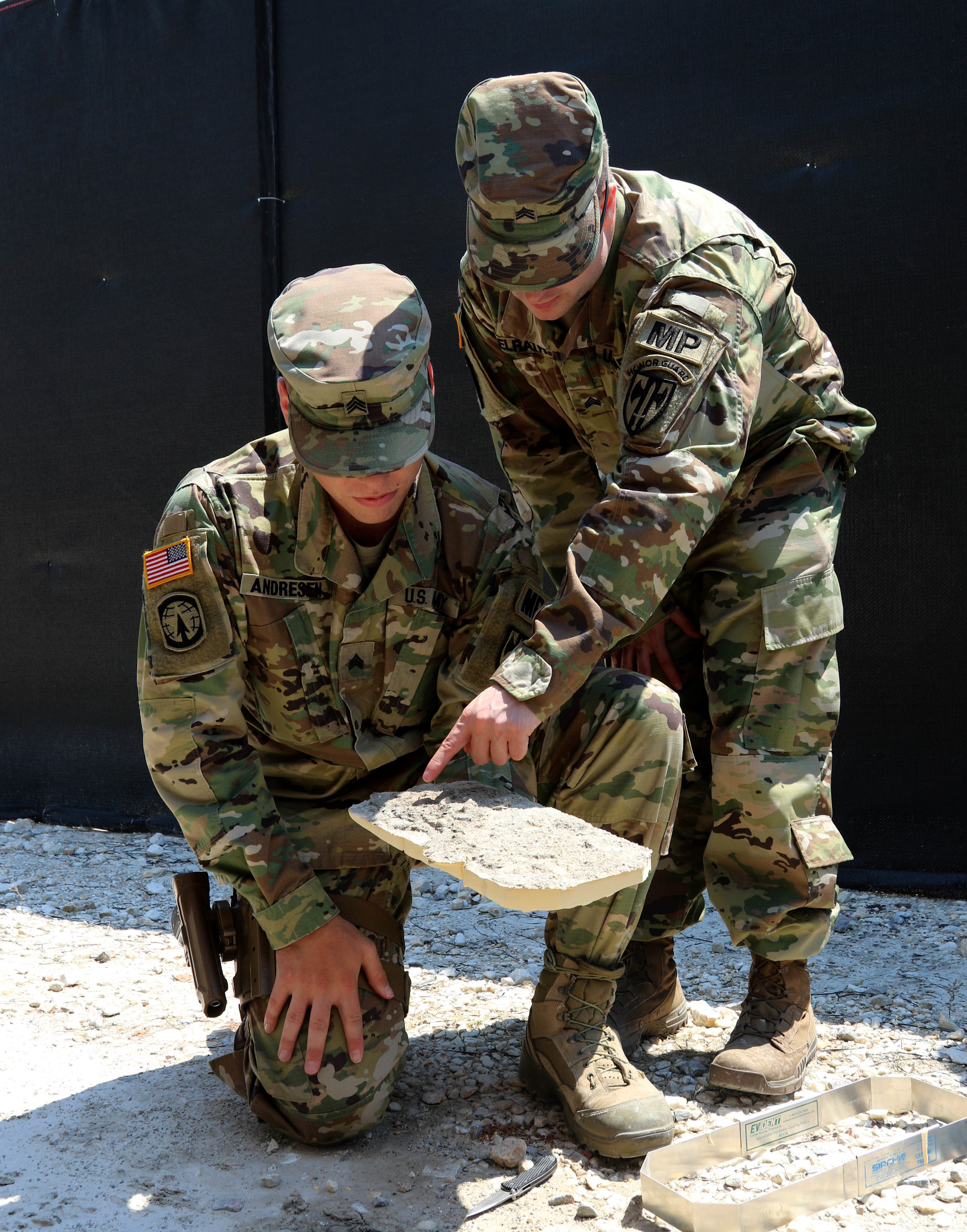 (Left-Right) Sgt. Michael Andresen and Sgt. Charles McElrath, both military policemen assigned to Multinational Battle Group-East, analyze a foot impression during a Crime Scene Investigation course held on Camp Bondsteel, Kosovo, July 13, 2016. (U.S. Army photo by: Staff Sgt. Thomas Duval, Multinational Battle Group-East public affairs)