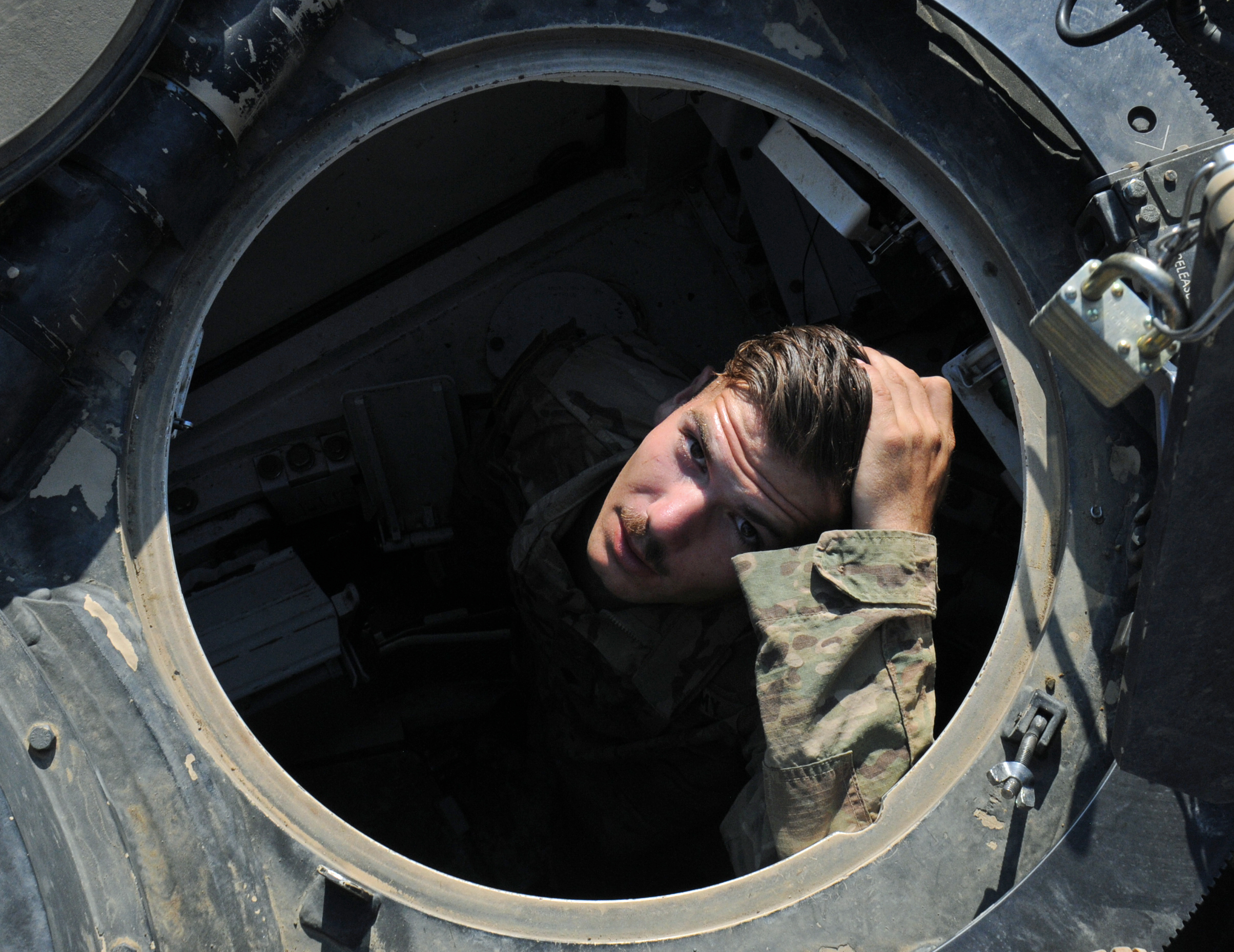 NOVO SELO TRAINIG AREA, Bulgaria – SPC Jonathan Cyr, Anvil Company, 1st Combined Arms Battalion, 64th Armor Regiment looks up from the hull of his tank July 21, 2016 as he gets ready to head out to the field with his company. The unit will spend 11-days in the field conducting platoon and company level situational training exercises (STX). 1st Bn., 64th Arm. Rgmt. is in Bulgaria in support of Operation Atlantic Resolve, a U.S. led effort in Eastern Europe that demonstrates U.S. commitment to the collective security of NATO and enduring peace and stability in the region.