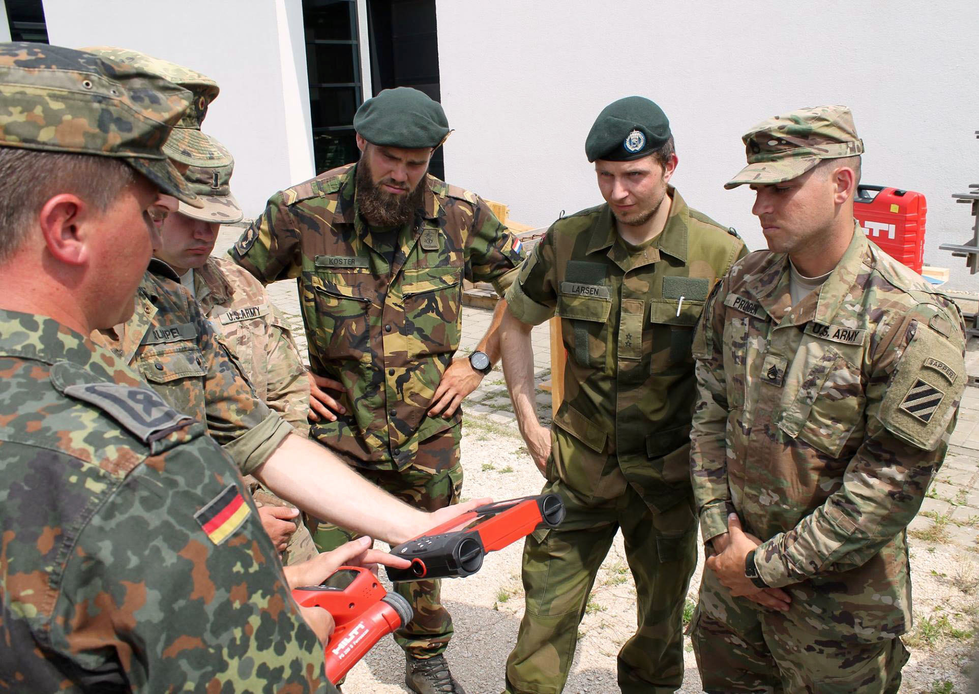 Staff Sgt. Craig Pruden, a combat engineer with 10th Engineer Battalion, 1st Armored Brigade Combat Team, 3rd Infantry Division, listens as German Soldiers talk about different equipment they use to assess bridges during a an International Bridge Assessment Course at Ingolstadt, Germany July 12. The course, a bilateral project from the Belgian and German engineer schools, supported by the Military Engineering Centre of Excellence, aims to inform Soldiers on the different existing bridge assessment methods.