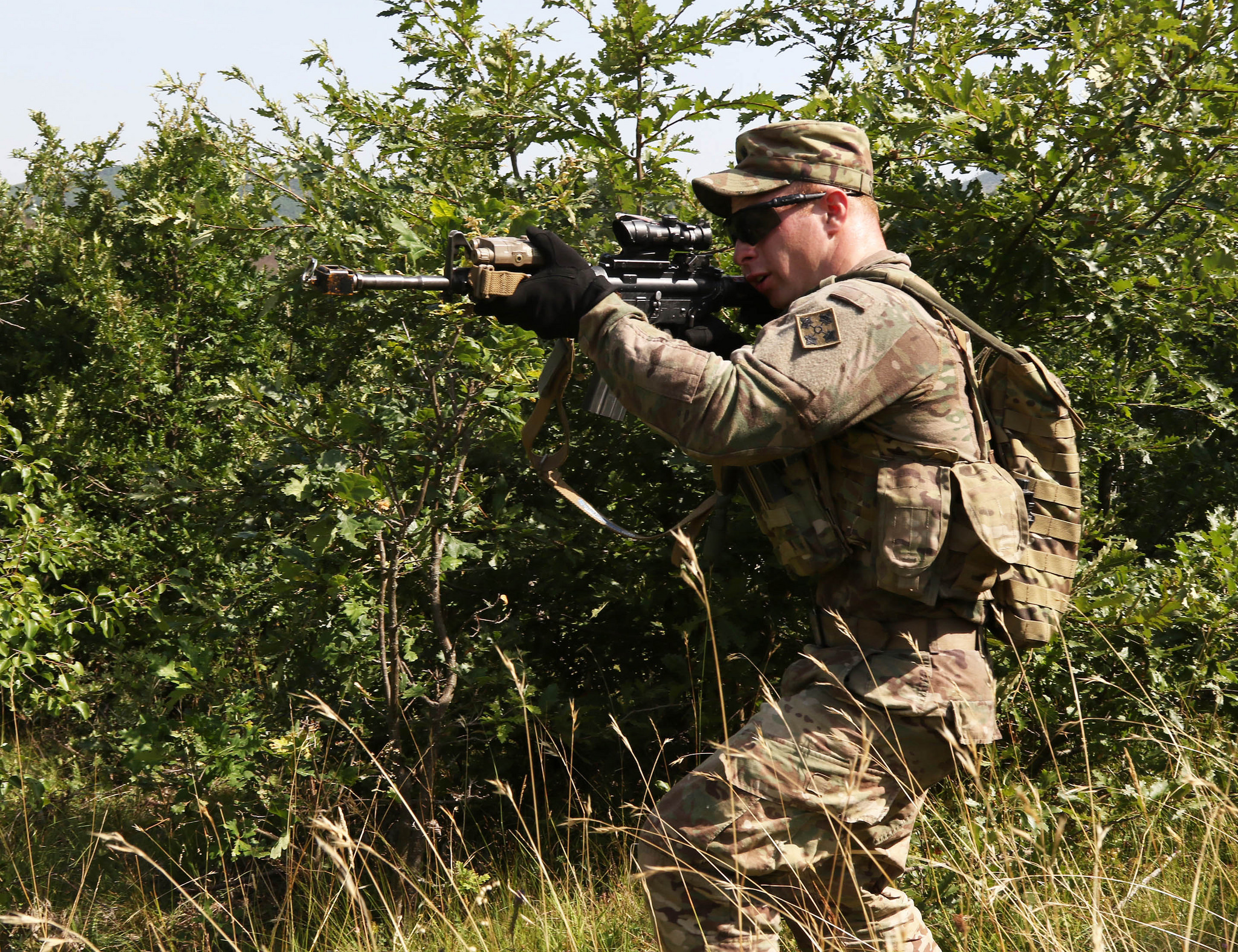 Spc. Timothy Squires, an infantryman assigned to the 1st Battalion, 41st Infantry Regiment, 2nd Infantry Brigade Combat Team, scans his sector of fire for any movement during a squad-level situational training exercise held in Dumnice, Kosovo, July 25, 2016. The purpose of the exercise was to train individual squad movements in preparation for a larger scale operation deemed Iron Eagle, later this year. (U.S. Army photo by: Staff Sgt. Thomas Duval, Multinational Battle Group-East Public Affairs)