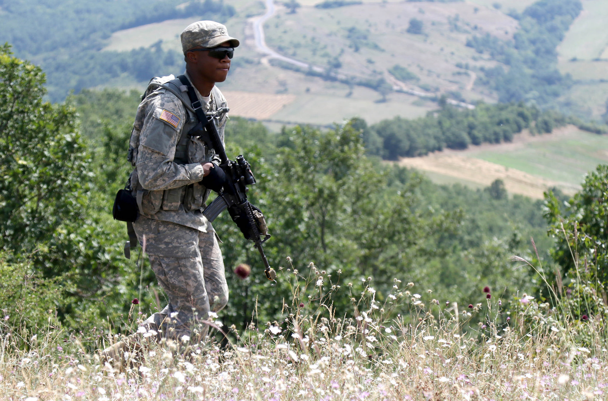 Pfc. Joshua Jones, an infantryman with the 1st Battalion, 41st Infantry Regiment, 2nd Infantry Brigade Combat Team, patrols a ridge line during a squad-level situational training exercise held in Dumnice, Kosovo, July 25, 2016. The purpose of the exercise was to train individual squad movements in preparation for a larger scale operation deemed Iron Eagle, later this year. (U.S. Army photo by: Staff Sgt. Thomas Duval, Multinational Battle Group-East Public Affairs)