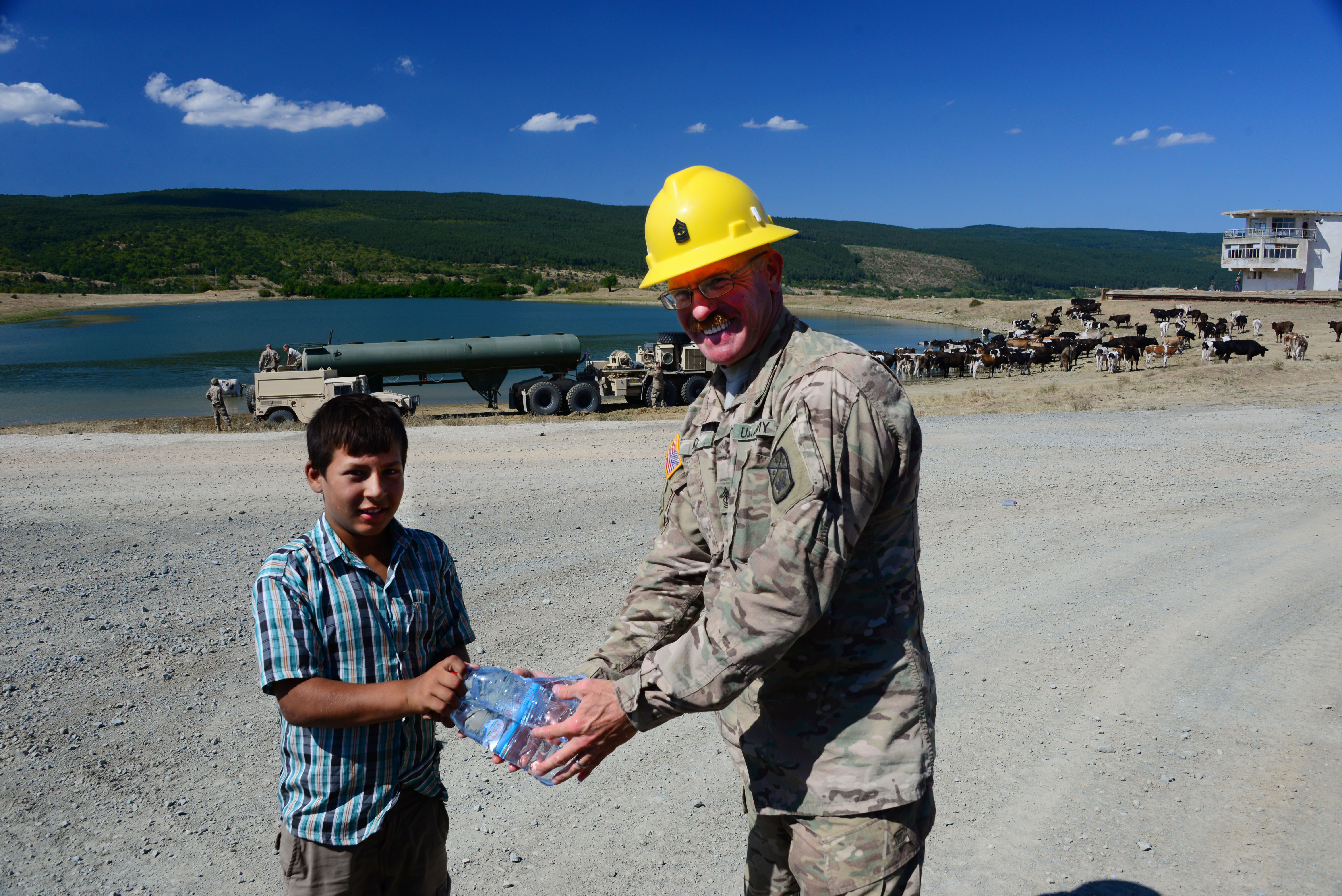 1st Sgt. Mike Ilko, 194th Engineer Brigade, Tennessee Army National Guard, shares bottled water with a young cattle herder Aug. 16, 2016, at Novo Selo Training Area, Bulgaria.  Local cattle and sheep herders regularly herd thier animals across NSTA.  Tennessee National Guard Soldiers and Airmen were on rotations to complete thier portions of projects as part of Operation Resolute Castle 16, an ongoing operation of military construction to build up Eastern European base infrastructure and help strengthen ties between Tennessee's state partnership with Bulgaria. (U.S. Air National Guard photo by Master Sgt. Kendra M. Owenby, 134 ARW Public Affairs)