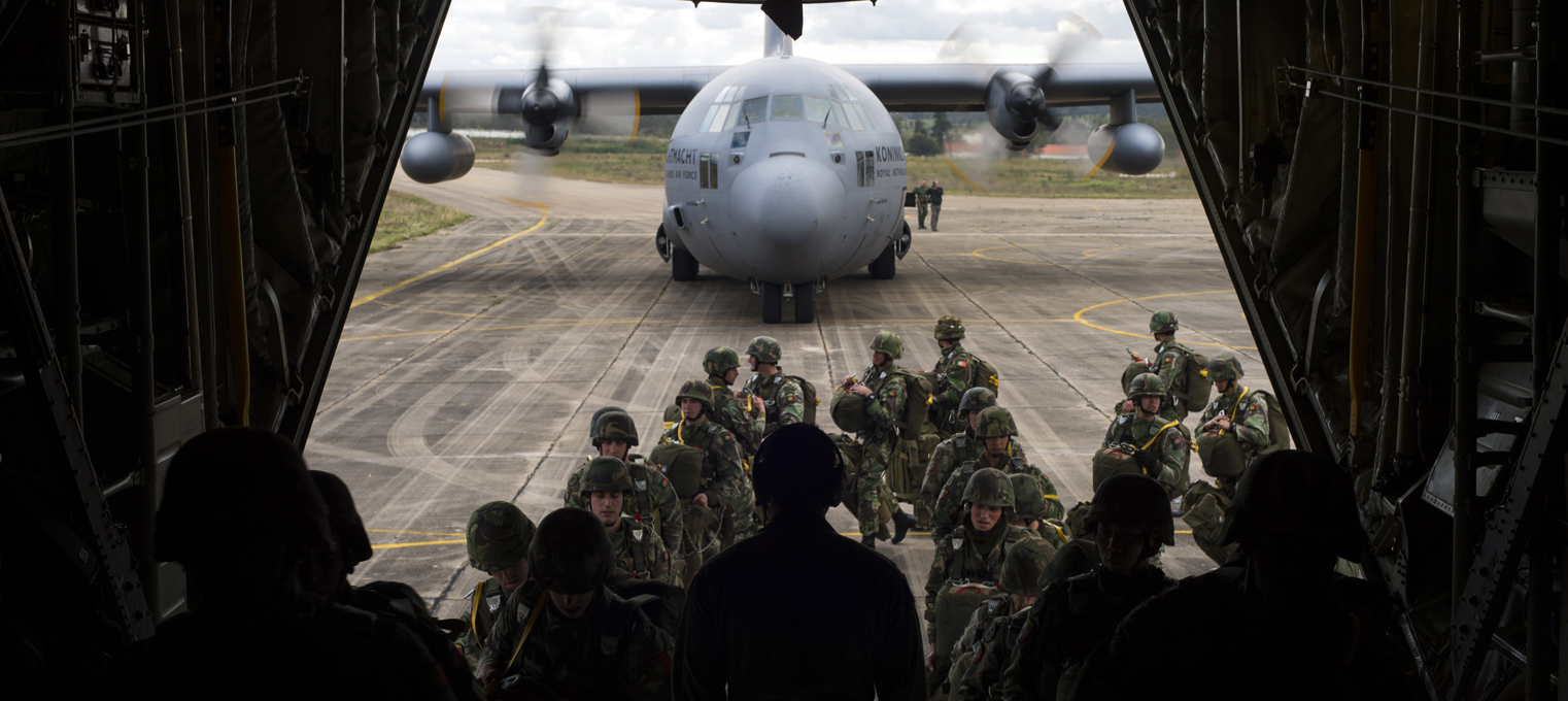 Portuguese paratroopers load onto a C-130J Super Hercules assigned to the 37th Airlift Squadron anda C-130H Hercules assigned to the Netherland air force during exercise Real Thaw 16 in Beja, Portugal, Feb. 25, 2016. The U.S. worked alongside the Royal Netherlands air force to airdrop more than 100 paratroopers. (U.S. Air Force photo/Senior Airman Jonathan Stefanko)