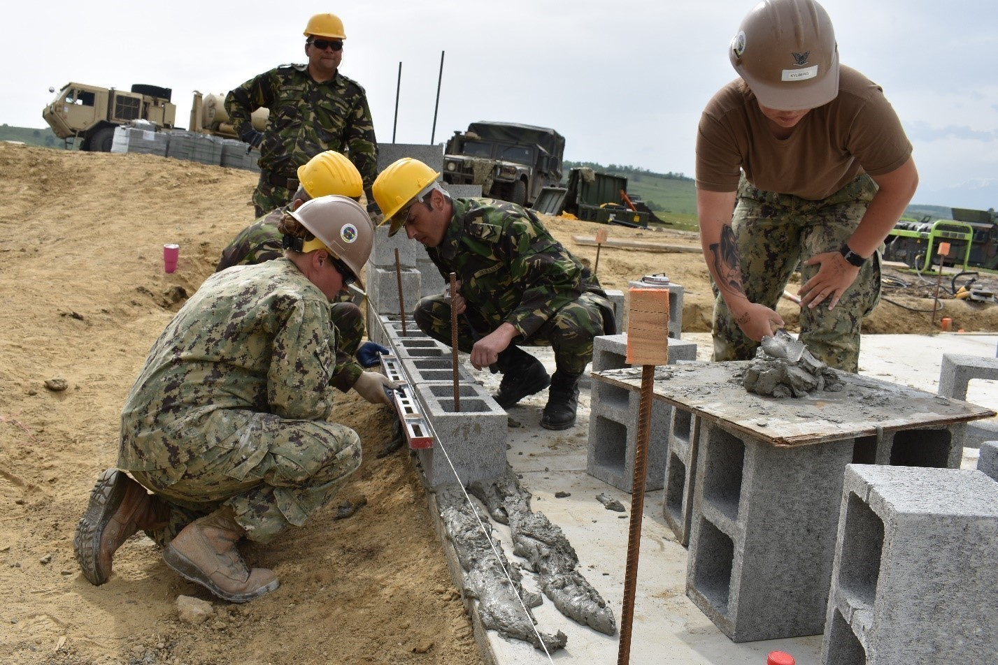 Builder 3rd Class Alexis Franklin works with Corporals Giurca, Szabo, and Vagu from the Romanian 10th Engineer Brigade as they place concrete blocks for the wall of an Operations and Storage Building as a part of Resolute Castle 17 at Joint National Training Center, Cincu, Romania, while Builder 3rd Class Samantha Kylberg provides mortar. Resolute Castle 17 is an exercise strengthening the NATO alliance and enhancing its capacity for joint training and response to threats within the region.
