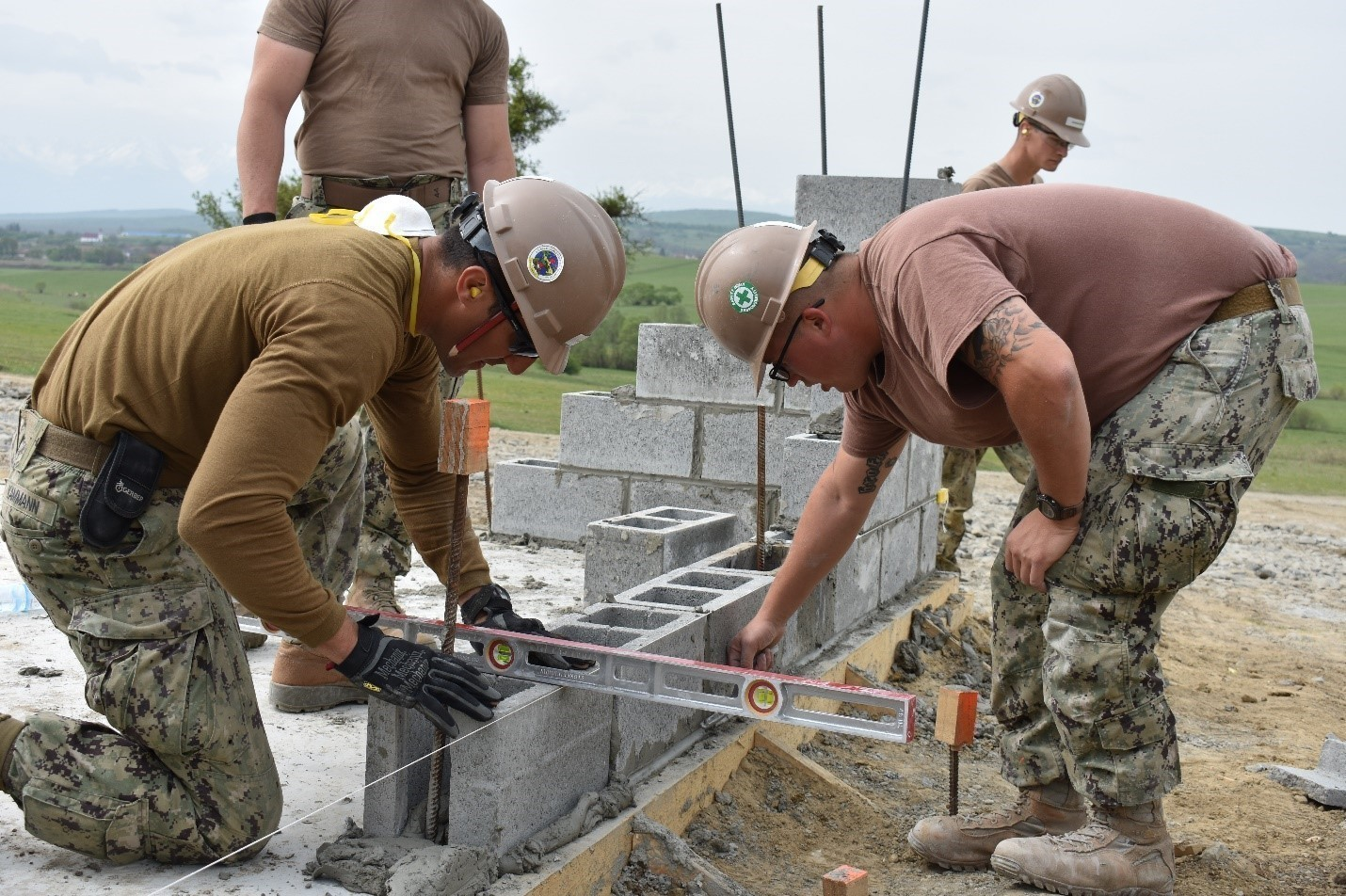 Constructionman, Construction Electrician Striker Jimmy Kammann and Steelworker 2nd Class Zachary McClellan level and place concrete blocks for the wall of an Operations and Storage Building as a part of Resolute Castle 17 at Joint National Training Center, Cincu, Romania. Resolute Castle 17 is an exercise strengthening the NATO alliance and enhancing its capacity for joint training and response to threats within the region.