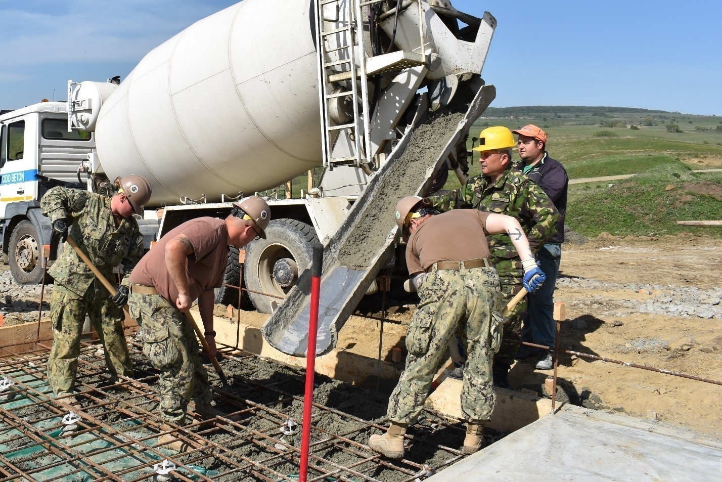 Builder 3rd Class Amanda Bryla, Builder 3rd Class Alexis Franklin, and Steel Worker 2nd Class Zachary McClellan of the Naval Mobile Construction Battalion 1 work with a soldier from the Romanian 10th Engineer Brigade emplace a concrete pad for an Operations and Storage Building as a part of Resolute Castle 17 at Joint National Training Center, Cincu, Romania. Resolute Castle 17 is an exercise strengthening the NATO alliance and enhancing its capacity for joint training and response to threats within the region.