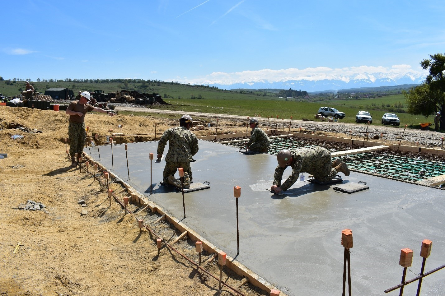 Senior Chief Joseph G. Daniel directs Builder 3rd Class Hector Juarez, Builder 3rd Class Samantha Kylberg, and Builder 3rd Class Alexis Franklin of the Naval Mobile Construction Battalion 1 as they level the concrete floor for an Operations and Storage Building as a part of Resolute Castle 17 at Joint National Training Center, Cincu, Romania.  Resolute Castle 17 is an exercise strengthening the NATO alliance and enhancing its capacity for joint training and response to threats within the region.