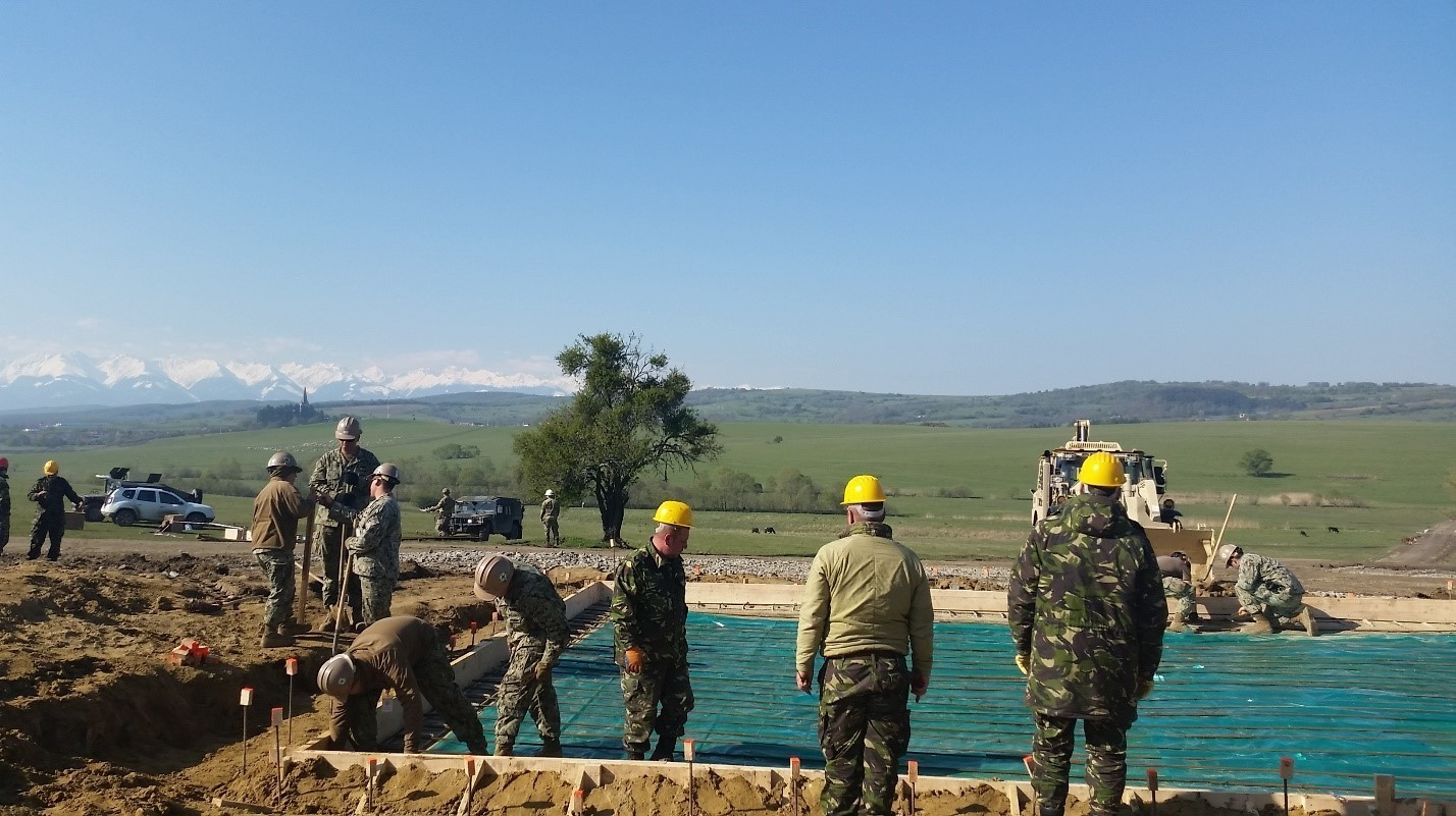 Sailors from the Naval Mobile Construction Battalion 1 work with soldiers from the Romanian 10th Engineer Brigade constructing an Operations and Storage Building as a part of Resolute Castle 17 at Joint National Training Center, Cincu, Romania.  The Seabees are laying down a vapor barrier and rebar prior to emplacing the concrete pad. Resolute Castle 17 is an exercise strengthening the NATO alliance and enhancing its capacity for joint training and response to threats within the region.
