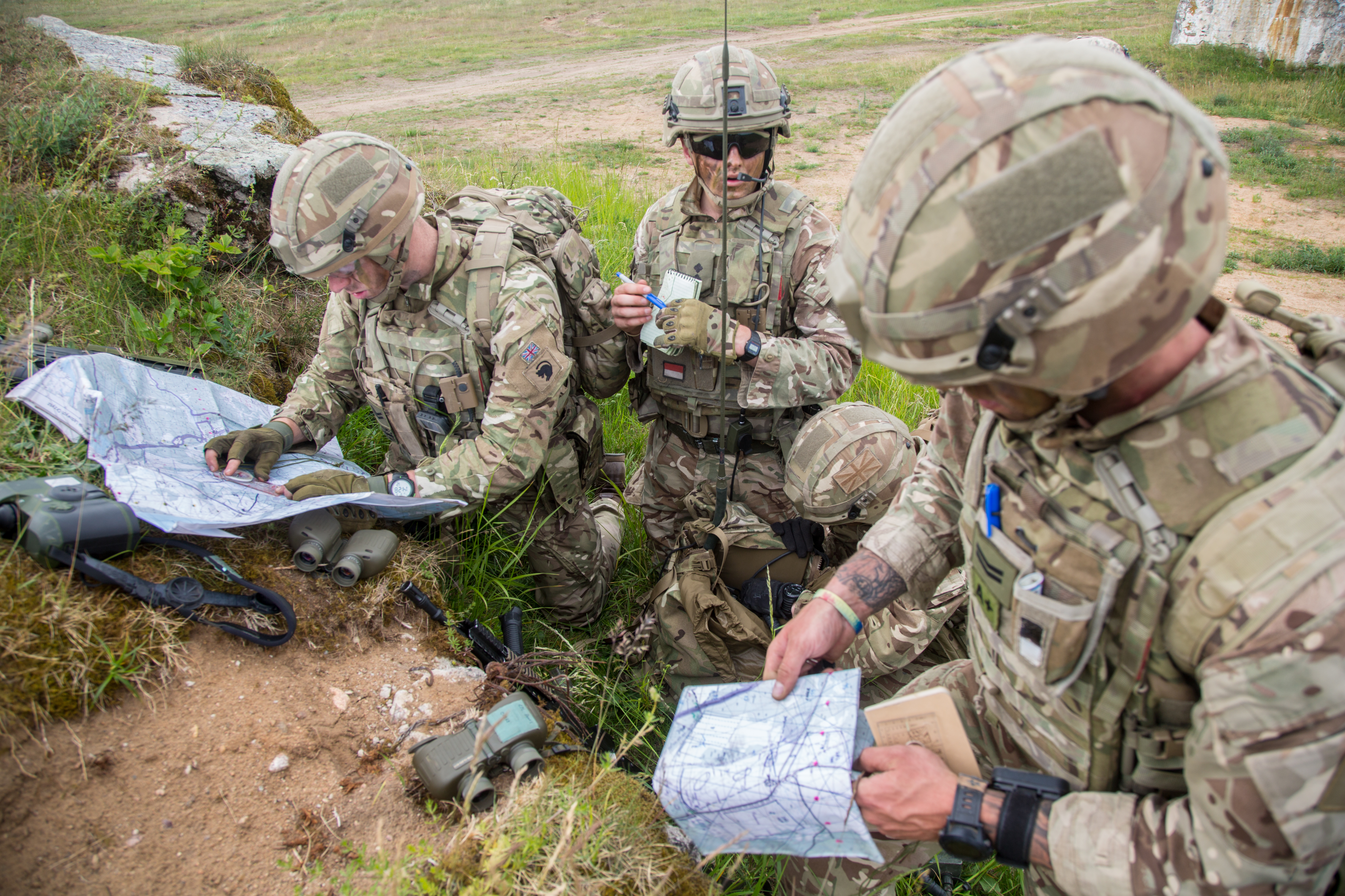 British Soldiers review maps to update coordinates and locate their positions during the Fire Support Coordination Exercise as part of the Saber Strike exercise at the Bemowo Piskie Training Area in Bemowo Piskie, Poland, June 6, 2017. The Saber Strike exercise facilitates cooperation and improves joint operational capability in a variety of missions and prepares the participating nations and units for future operations while enhancing the NATO alliance. (U.S. Army photo by Spc. Stefan English)