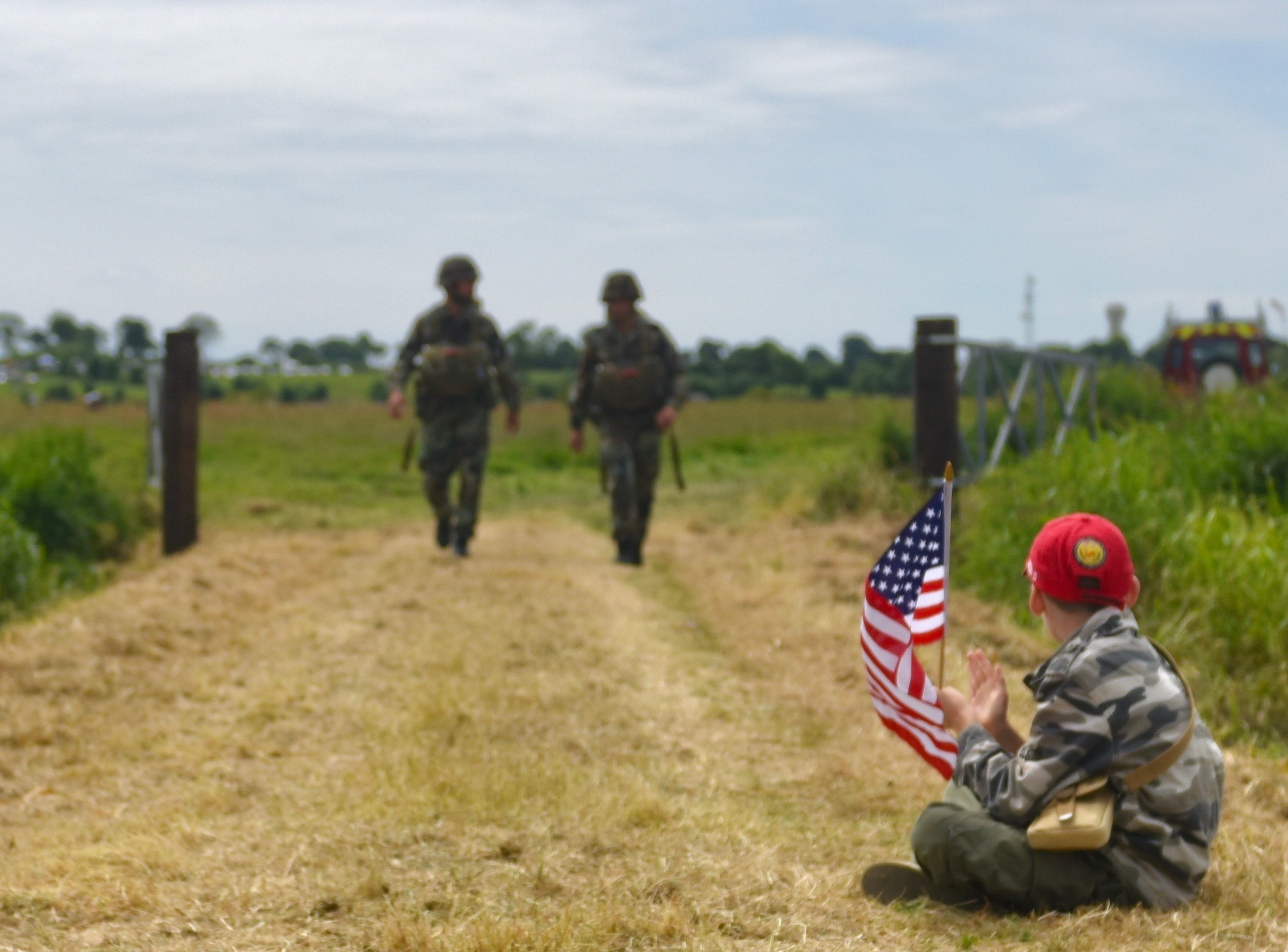 A young French spectators eagerly claps and awaits for two Paratroopers as they come off the drop zone following the commemorative jump by airborne forces into Normandy France for D-Day 73. 