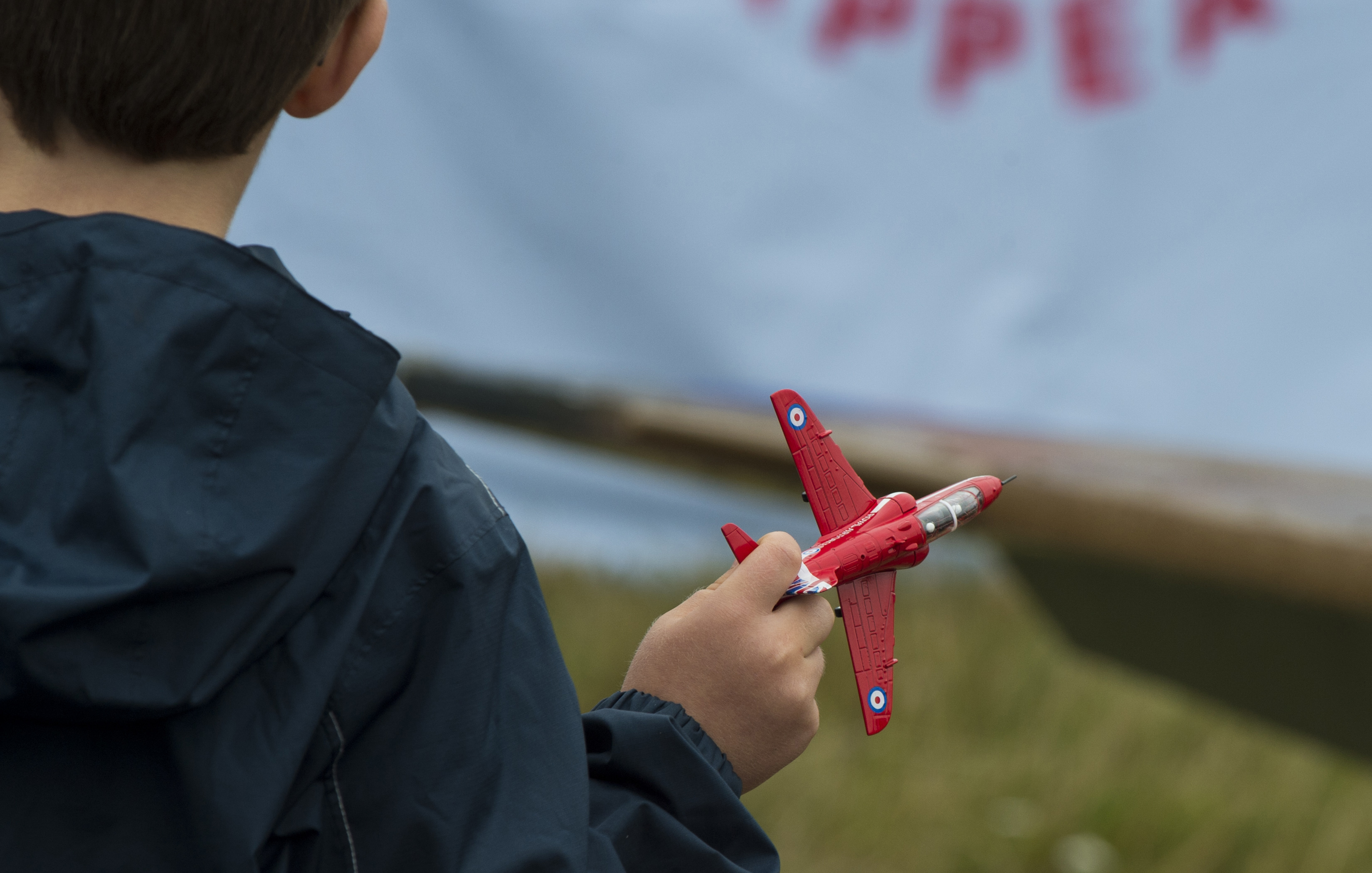 FAIRFORD, United Kingdom – A young boy flies his toy Royal Air Force Red Arrow Hawk T1 during the 2017 Royal International Air Tattoo (RIAT) located at RAF Fairford, United Kingdom, on July 15, 2017. This year commemorates the U.S. Air Force's 70th Anniversary which was highlighted during RIAT by displaying its lineage and advancements in military aircraft. (U.S. Air Force Photo by Tech. Sgt. Brian Kimball)