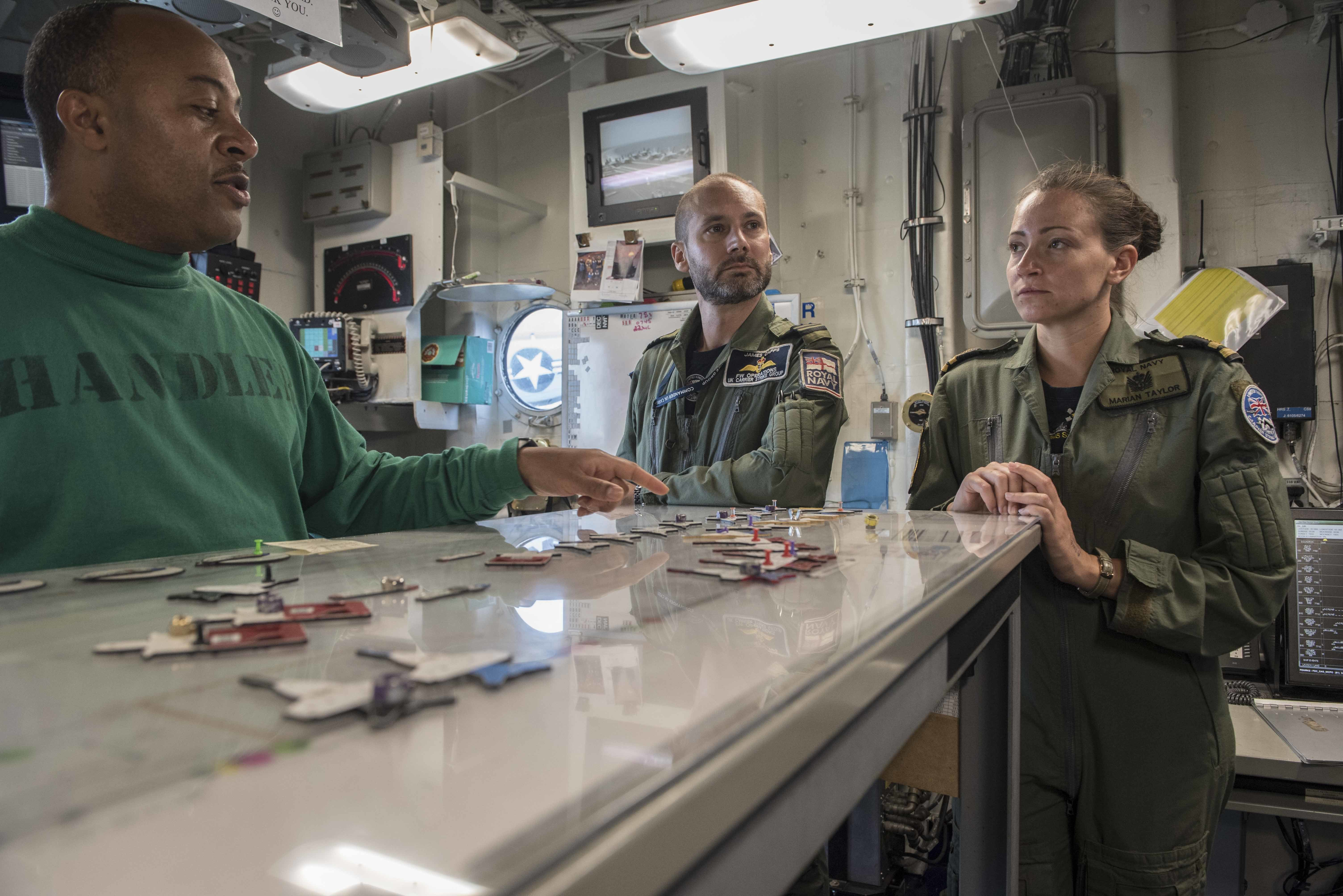 170721-N-AJ467-240 MEDITERRANEAN SEA (July 22, 2017) Lt. Cmdr. Winston Cotterell, aircraft handling officer aboard USS George H.W. Bush (CVN 77), explains flight deck operations to Royal Navy (RN) Lt. Cdr. James Capps and RN Lt. Marian Taylor, both from the U.K. Carrier Strike Group, in Flight Deck Control. The officers from the UKCSG are embarked in preparation for Exercise Saxon Warrior, a keystone exercise as the U.K. prepares for the arrival of the HMS Queen Elizabeth. The GHWB and its carrier strike group are conducting naval operations in the U.S. 6th Fleet area of operations in support of U.S. national security interests in Europe and Africa. (U.S. Navy photo by Mass Communication Specialist Seaman Darien Weigel/Released)