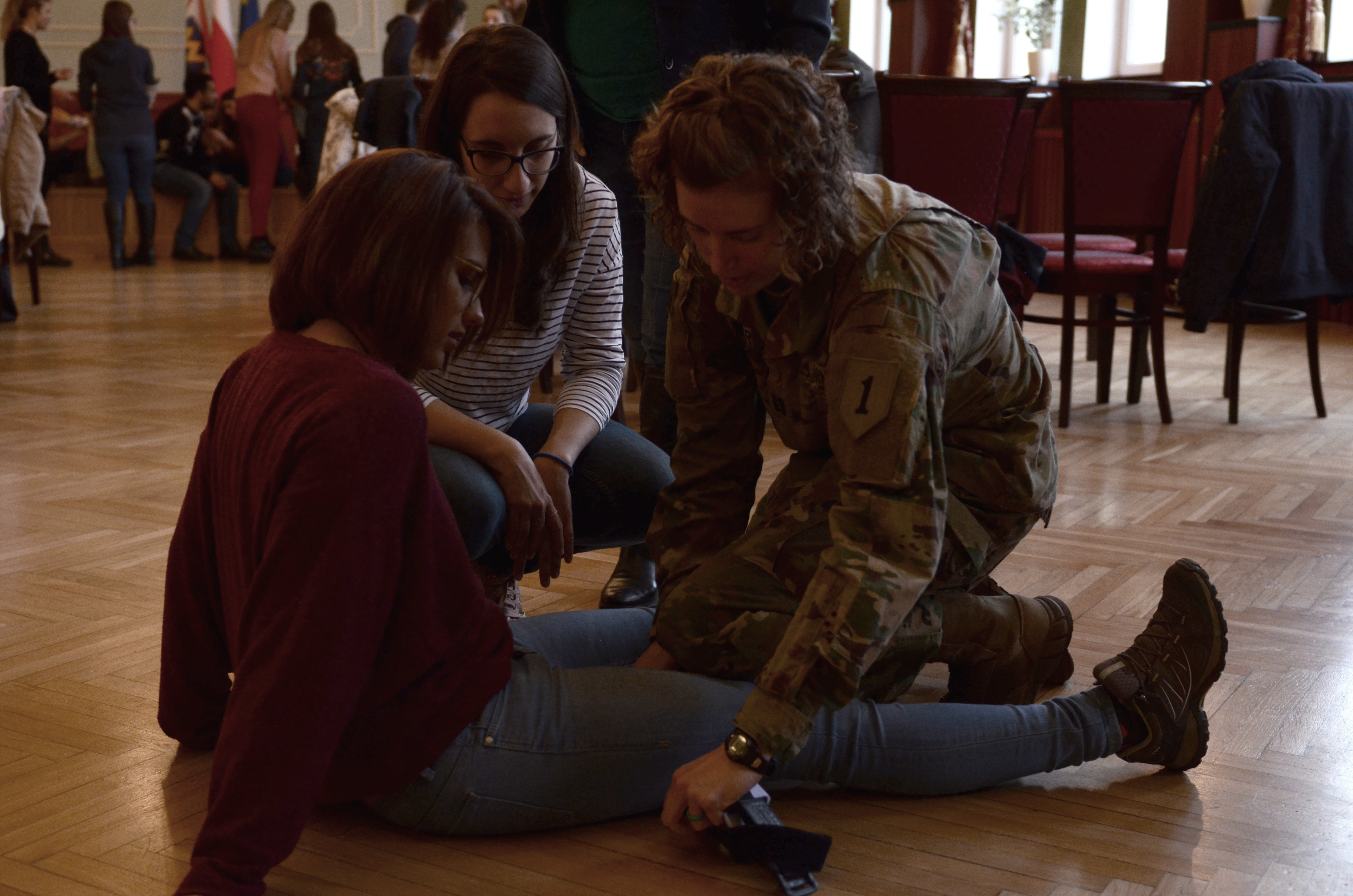 ŻARY, Poland — U.S. Army Capt. Jade Snader, brigade nurse, 299th Brigade Support Battalion, 2nd Armored Brigade Combat Team, 1st Infantry Division, demonstrates how to apply a tourniquet on the thigh, in a first aid class, city hall, Żary, Poland, Nov. 2. The class is taught by U.S. Soldiers from 2nd Armored Brigade Combat Team, 1st Infantry Division, and Polish soldiers from 34th Armored Cavalry Brigade, 11th Armored Cavalry Division. The class of 40 representatives attend the European Union project called Collaborative Consumption- Versus Wasting. The class is a refresher course to instill knowledge and confidence in participants to take life-saving action in unexpected emergencies. The  2nd Armored Brigade Combat Team, 1st Infantry Division, is currently in Europe to support Atlantic Resolve. Atlantic Resolve is a U.S. endeavor to fulfill NATO commitments by rotating U.S. -based units throughout the European theater and training with NATO Allies and partners. (U.S. Army photo by Sgt. Shiloh Capers)