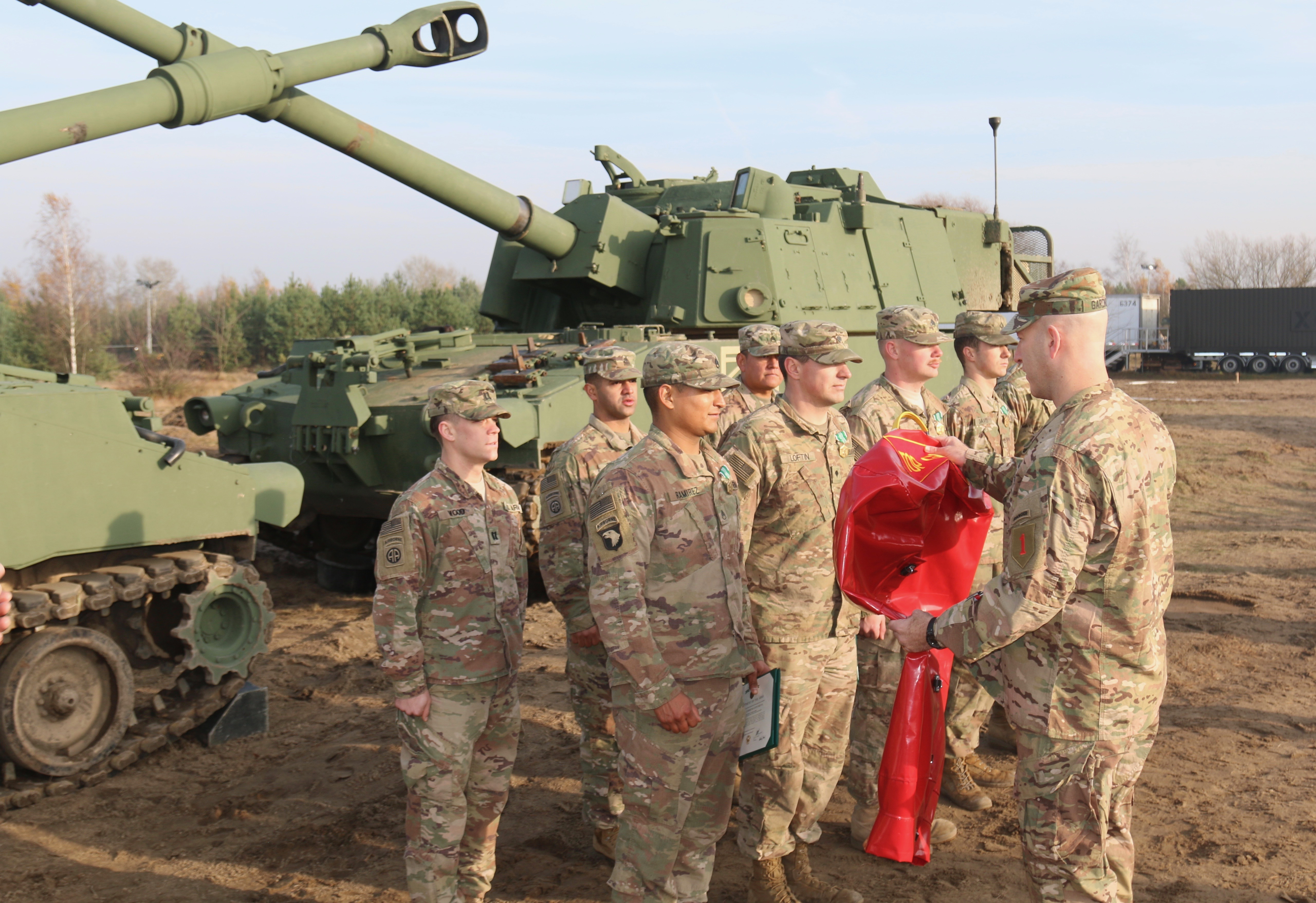 TORUN, Poland—Soldiers from 1st Battalion, 7th Field Artillery Regiment, 'Lightning Battalion,' 2nd Armored Brigade Combat Team, 1st Infantry Division, receive a special muzzle cover from Commander, Col. David Gardner, 2nd ABCT, for winning the Top Gun competition, Nov. 23 in Torun, Poland. Lightning Battalion conducted a 'Top Gun/Top FDC' competition, Nov. 19-23, to determine the best artillery gun crew and fire direction center in the battalion. The event was designed to promote esprit de corps and sustain their readiness and ability to deliver timely and accurate fires. (Photo by Capt. Orlandon Howard)