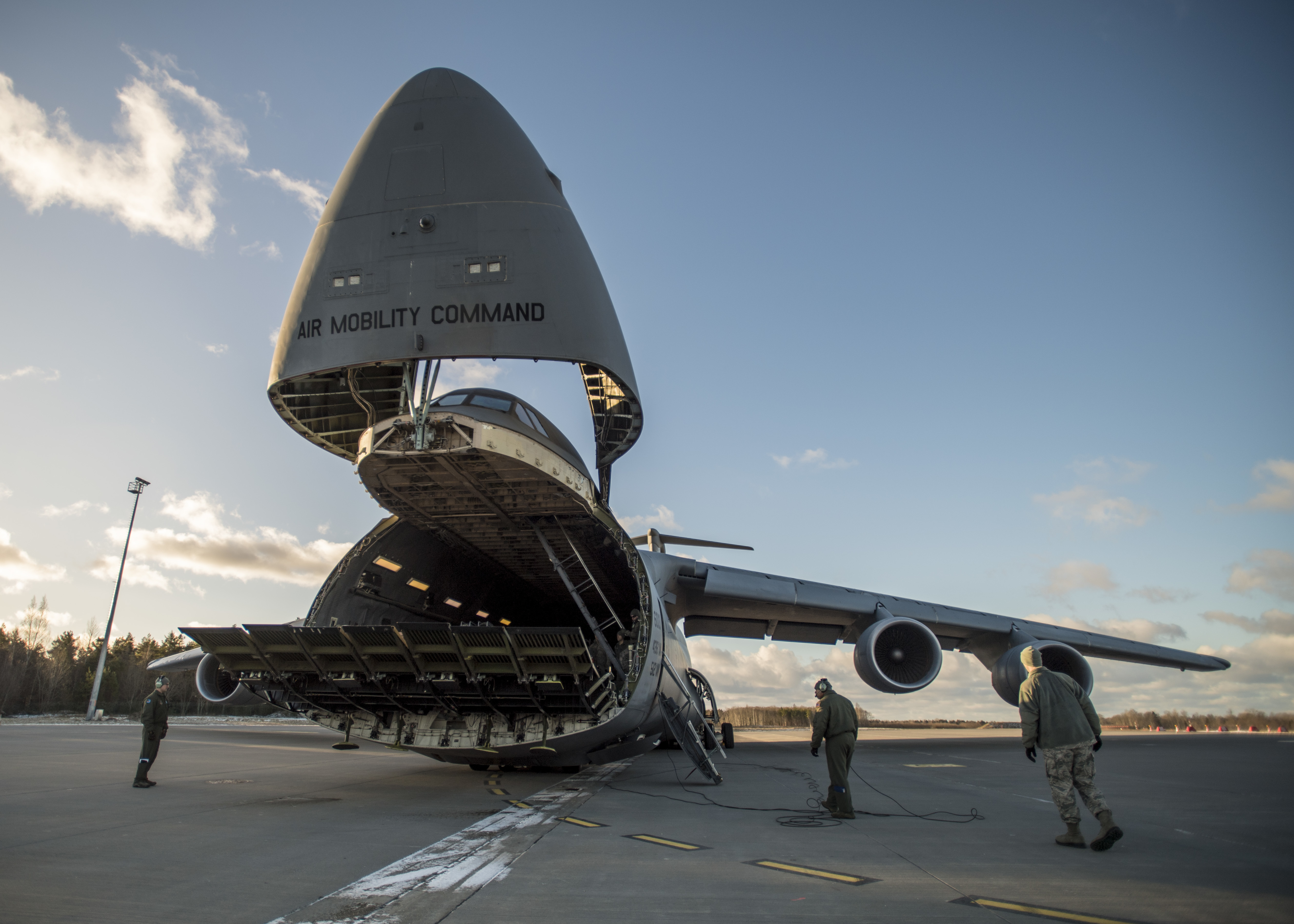U.S. Airmen get ready to receive the supplies from a C-5 Galaxy cargo plane that were delivered in support of the Theater Security Package 18.1, Jan. 8, 2018. This TSP highlights the U.S.'s ability to deploy fighter aircraft to support our partners and allies in the European theater and around the world. (DoD photo by MC3 Cody Hendrix)