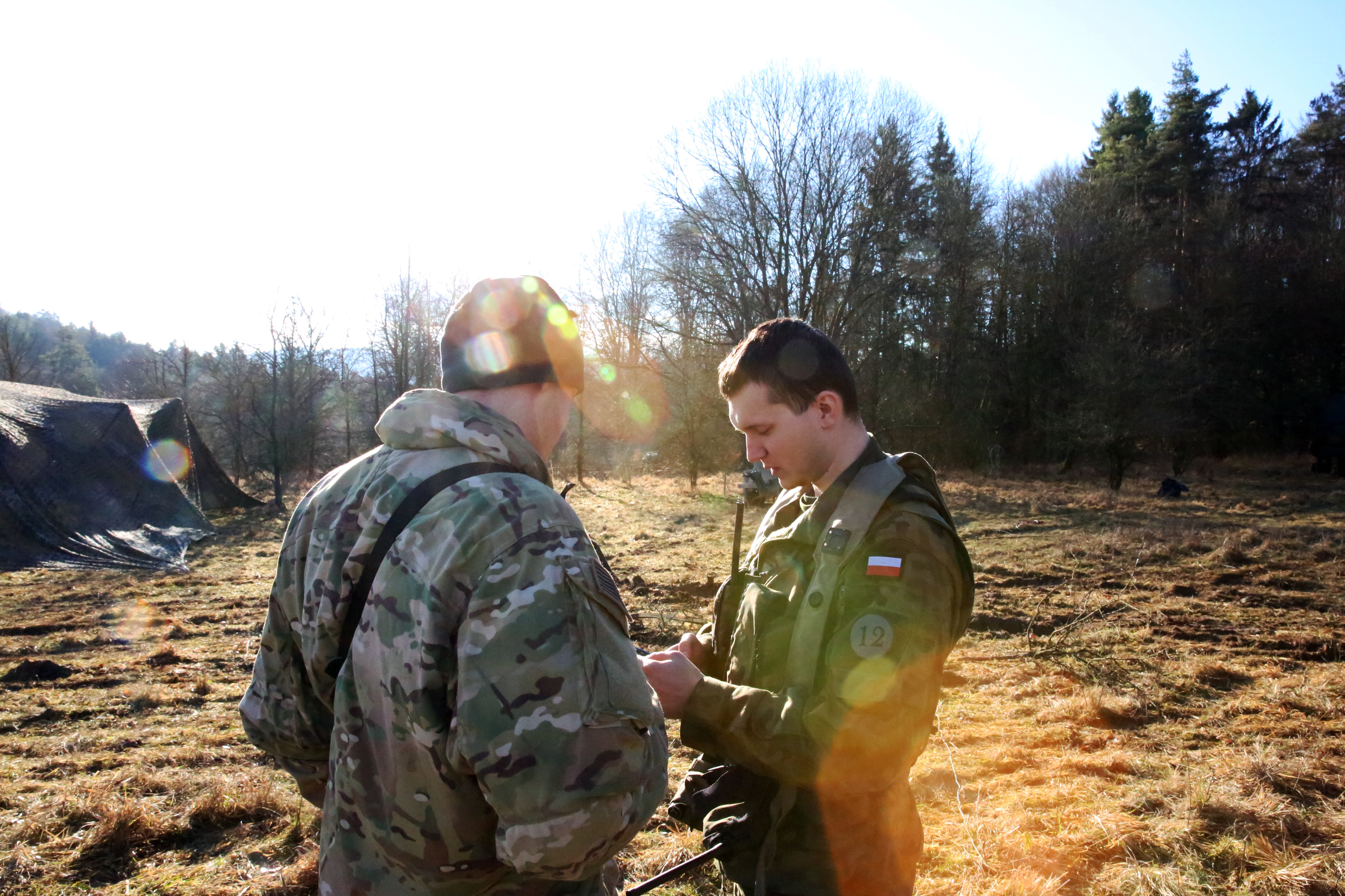U.S. Army 2nd Lt. Justin Hortin, a platoon leader assigned to Charlie Company, 44th Expeditionary Signal Battalion, 2nd Theater Signal Brigade, speaks with a Polish Army officer during exercise Allied Spirit VIII, Jan. 31, 2018 in the Hohenfels Training Area, Germany. (U.S. Army photo by William B. King)
