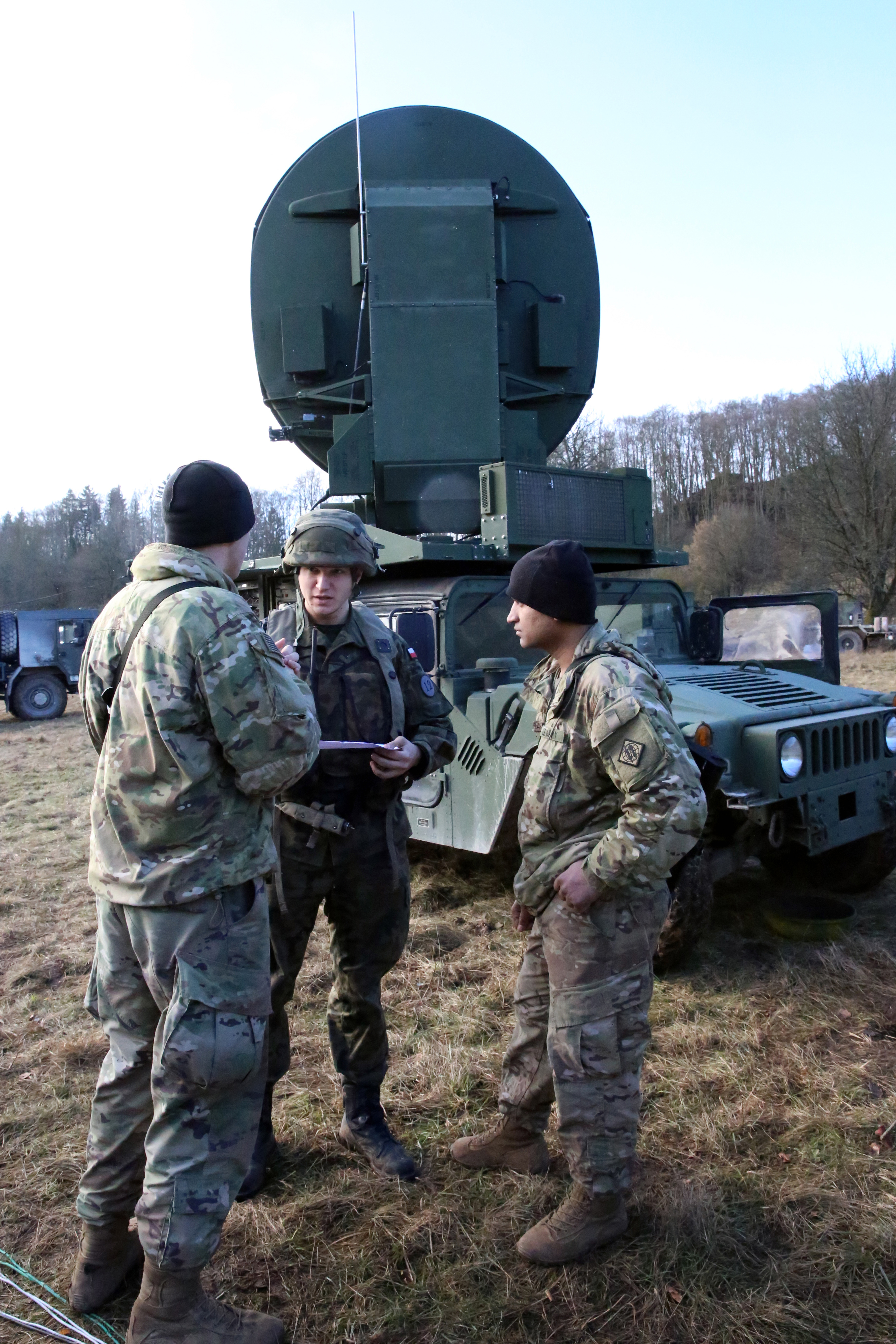 U.S. Army 2nd Lt. Justin Hortin (left), a platoon leader assigned to Charlie Company, 44th Expeditionary Signal Battalion, 2nd Theater Signal Brigade, and platoon sergeant Staff Sgt. Asif Mubarak, speak with a Polish Army officer during exercise Allied Spirit VIII, Jan. 31, 2018 in the Hohenfels Training Area, Germany. (U.S. Army photo by William B. King)