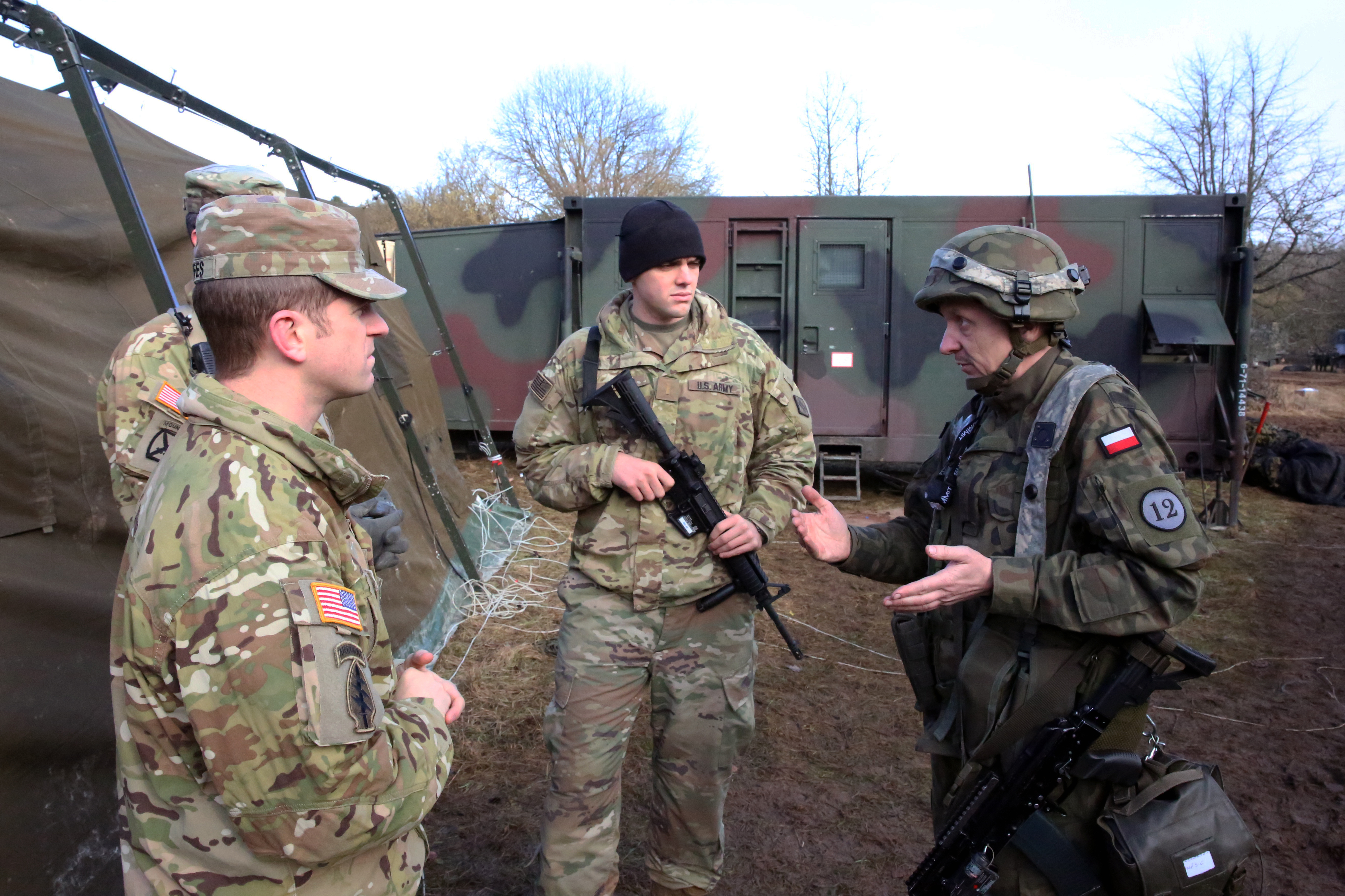 U.S. Army Capt. James Griffes (left), commander of Charlie Company, 44th Expeditionary Signal Battalion, 2nd Theater Signal Brigade, and platoon leader 2nd Lt. Justin Hortin speak with Maj. Tomsz Koczalski, the S-6 Communications and Information Management officer assigned to Poland's 12th Mechanized Brigade, during exercise Allied Spirit VIII, Jan. 31, 2018 in the Hohenfels Training Area, Germany. (U.S. Army photo by William B. King)