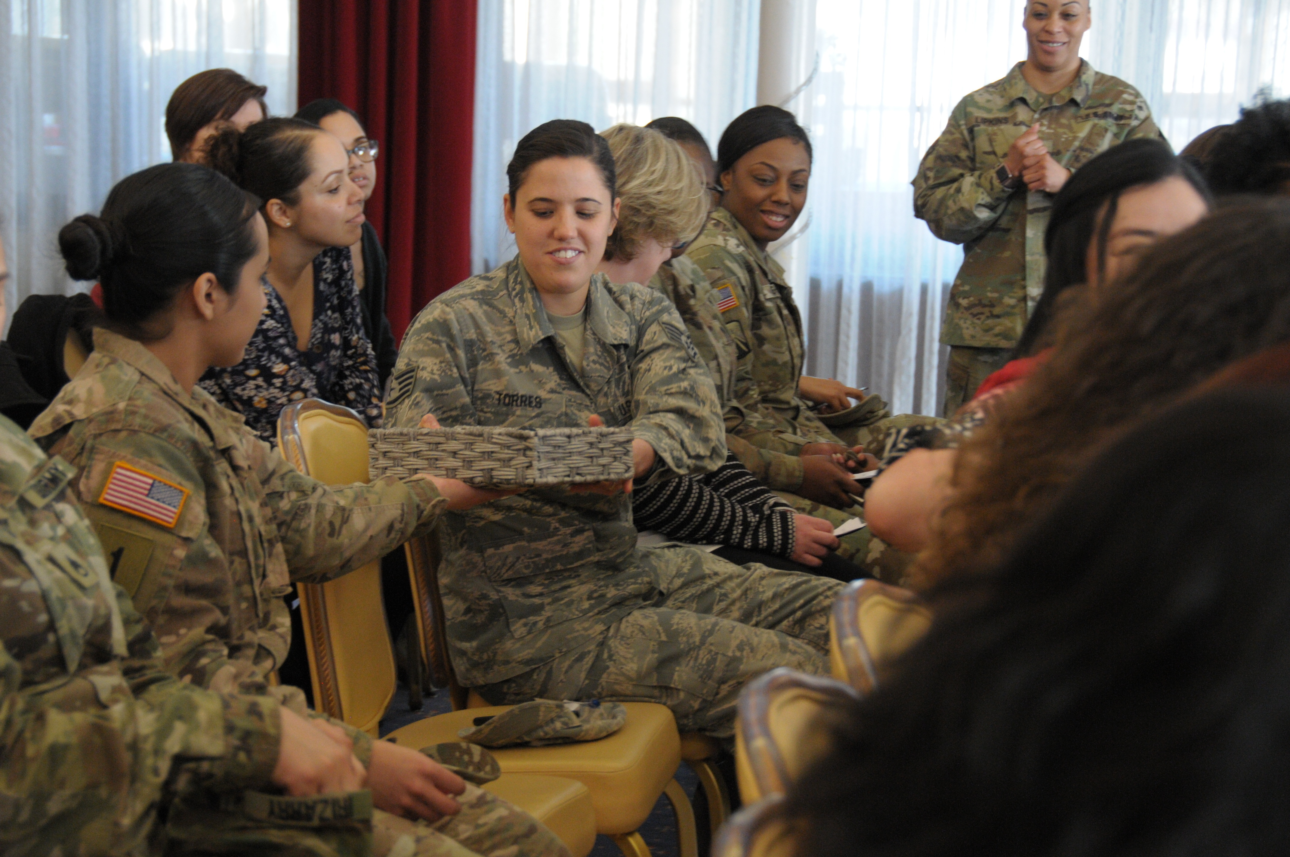 Staff Sgt. Emily Torres reaches for the weighted basket to demonstrate how through team work, she can help unload and carry the weight of her fellow Sisters-in-Arms, March 5 at the Sisters-in-Arms meet and greet located at the Armstrong's Club on Vogelweh housing complex.