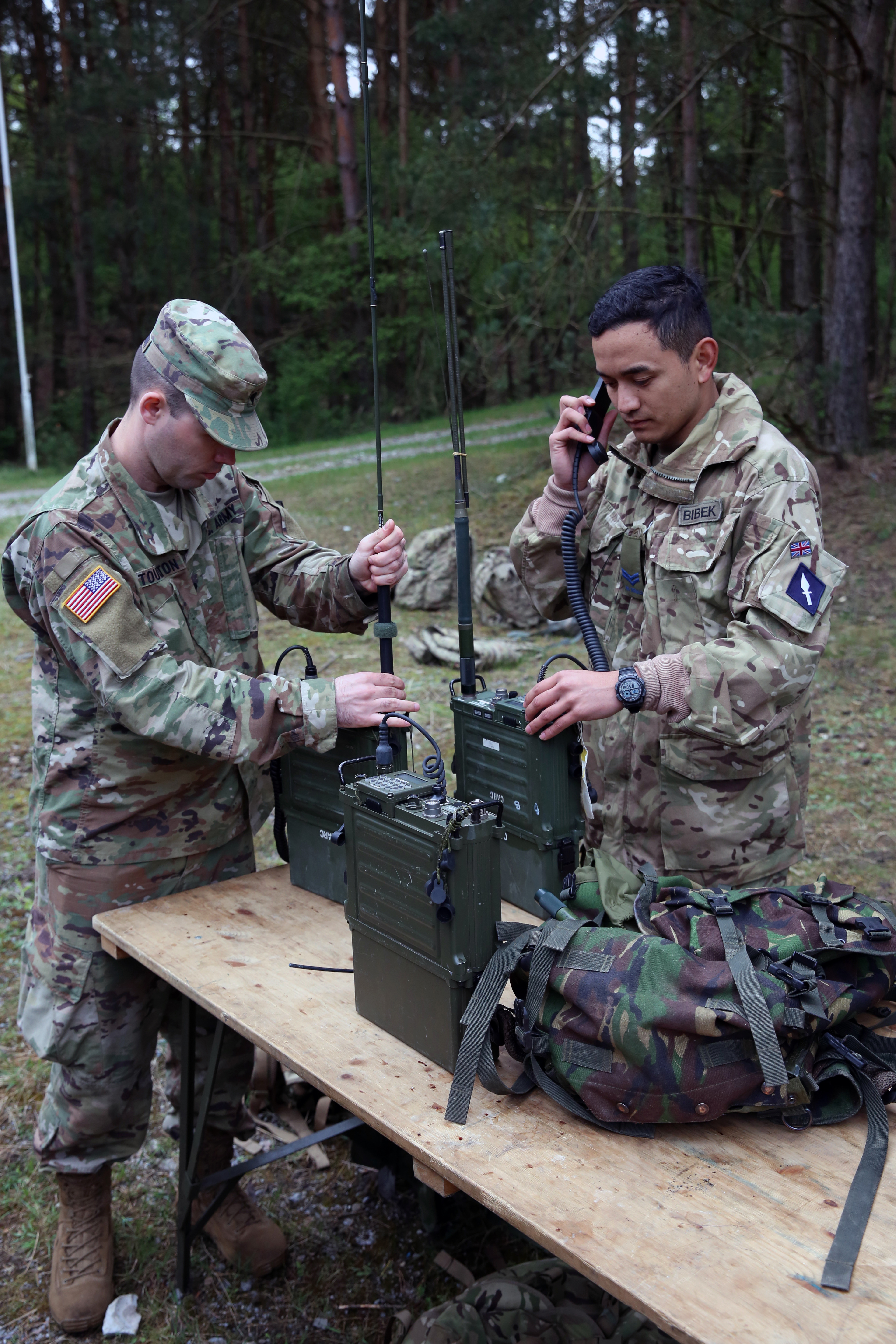 U.S. Army Spc. Jerrod Touchton, assigned to Bravo Company, 44th Expeditionary Signal Battalion, 2nd Theater Signal Brigade, and British Army Cpl. Bibek Gurung, assigned to the 250th Signal Squadron, Queen's Gurkha Signals, set up radios and test communications during exercise Stoney Run, April 24, 2018 in the Sennelager Training Area, Germany. Stoney Run is an annual U.S.-U.K. signal exercise designed to test and validate communications and network capabilities, and enhance interoperability and partner capacity between the two NATO allies. (U.S. Army photo by William B. King)