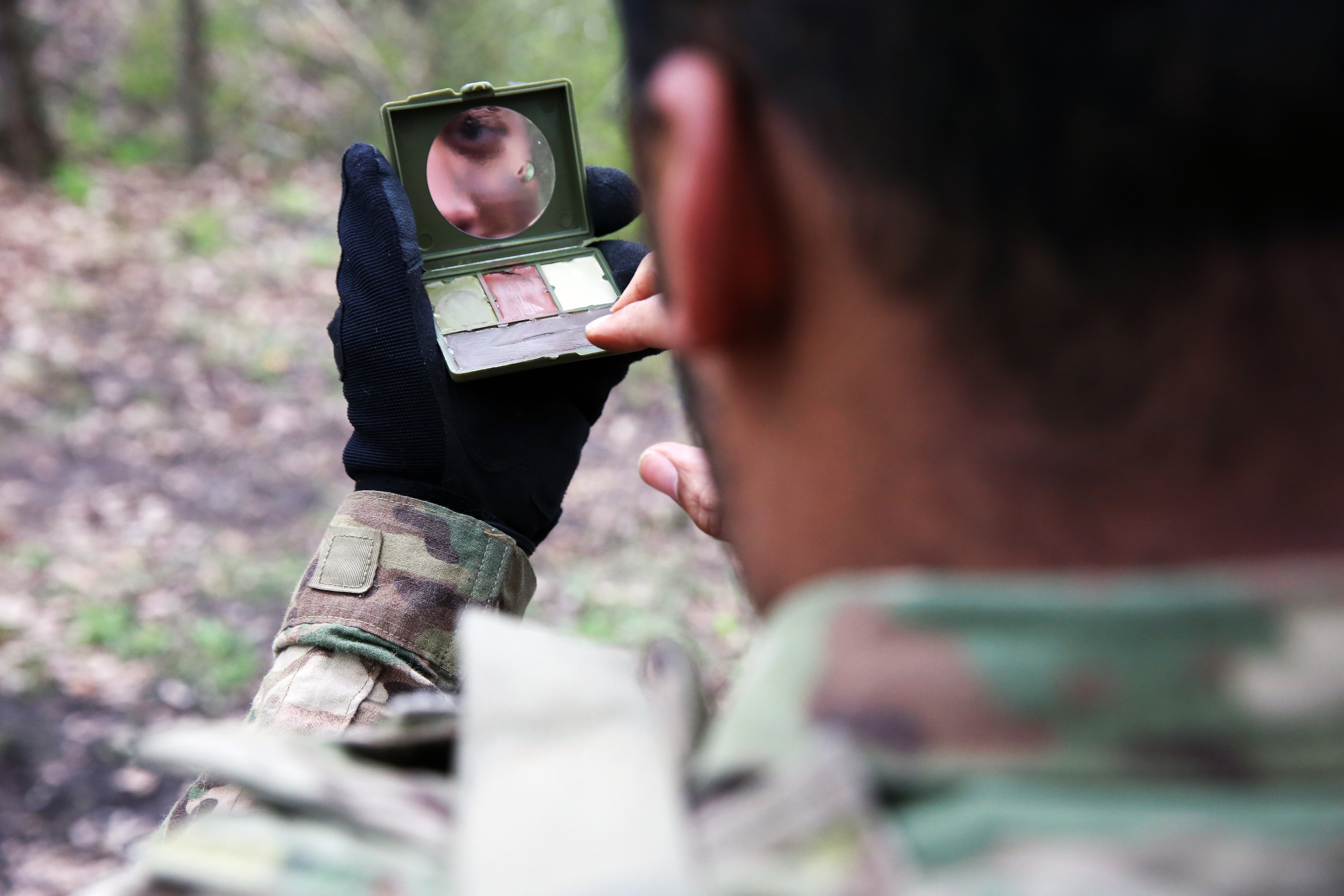 U.S. Army Spc. Christian Summers, assigned to Bravo Company, 44th Expeditionary Signal Battalion, 2nd Theater Signal Brigade, looks in the mirror as he applies comouflage paint during exercise Stoney Run, April 24, 2018 in the Sennelager Training Area, Germany. Stoney Run is an annual U.S.-U.K. signal exercise designed to test and validate communications and network capabilities, and enhance interoperability and partner capacity between the two NATO allies. (U.S. Army photo by William B. King)