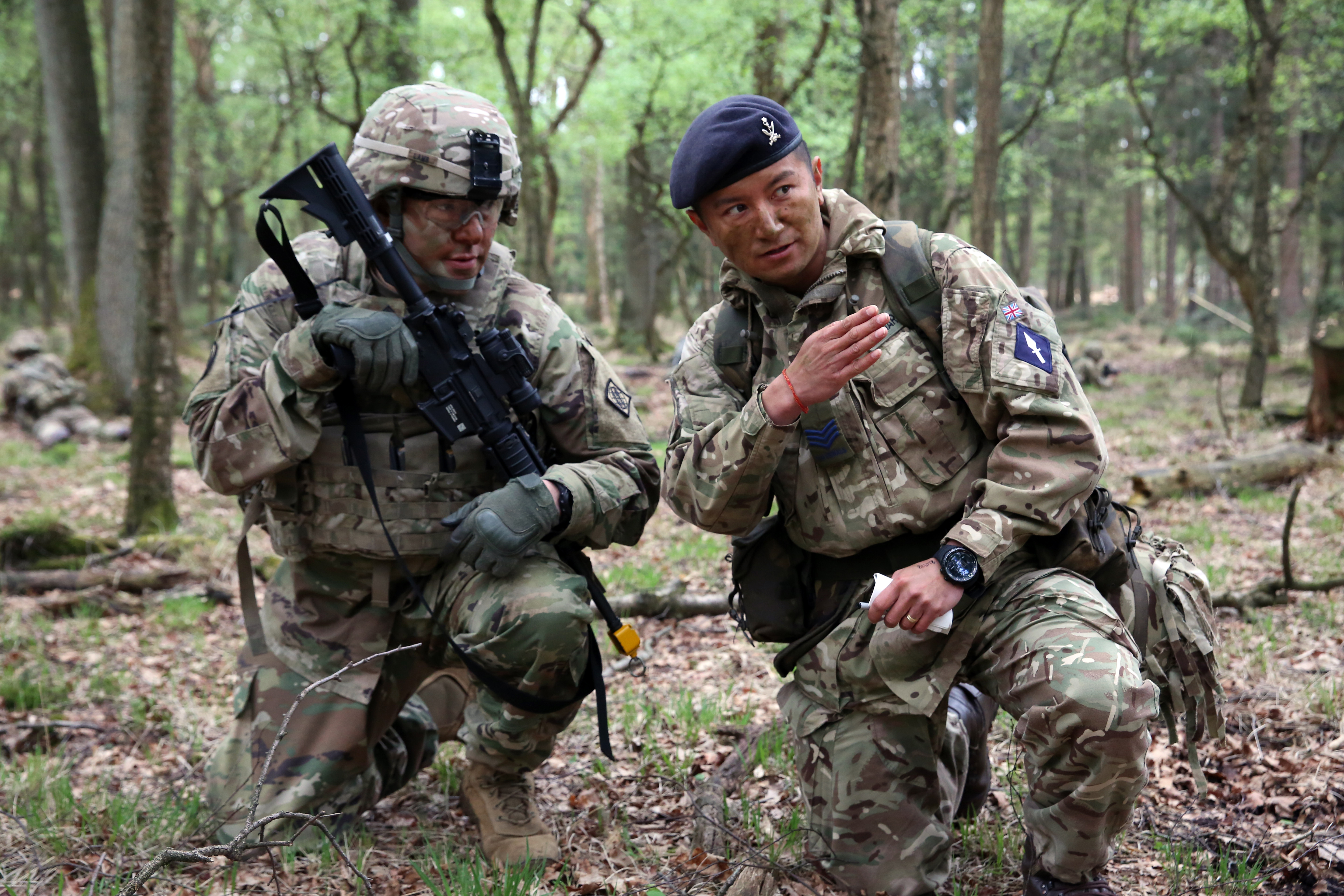 British Army Sgt. Thapa Kumar, assigned to the 250th Signal Squadron, Queen's Gurkha Signals, instructs U.S. Army Staff Sgt. Jeffery Lamb, assigned to Bravo Company, 44th Expeditionary Signal Battalion, 2nd Theater Signal Brigade, during a joint tactical patrol during exercise Stoney Run in the Sennelager Training Area, Germany, April 24, 2018. Stoney Run is an annual U.S.-U.K. signal exercise designed to test and validate communications and network capabilities, and enhance interoperability and partner capacity between the two NATO allies. (U.S. Army photo by William B. King)
