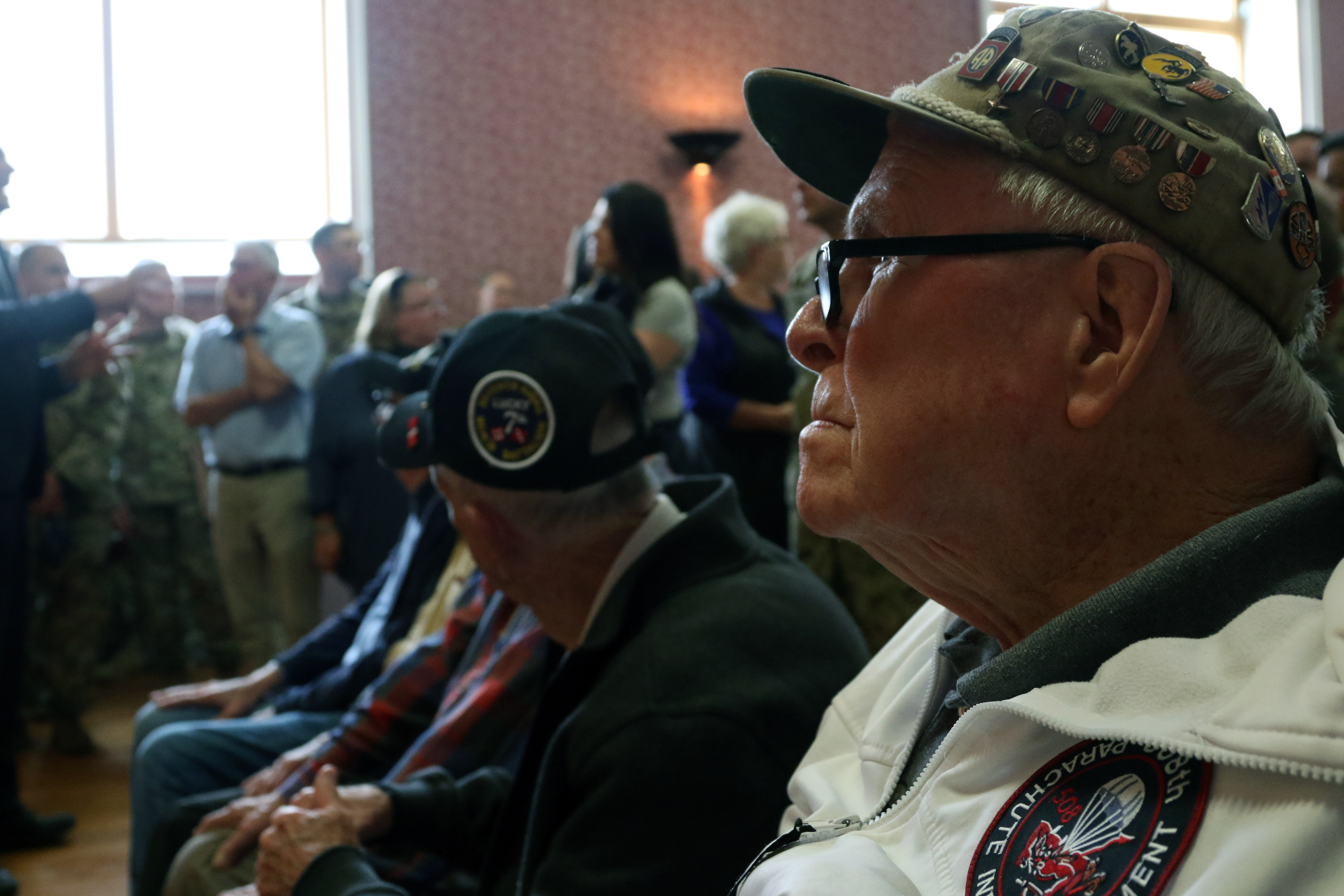 WWII veteran, George Shankle (front), a radio operator with Co. E., 508th Parachute Infantry Regiment, 1st Brigade Combat Team, 82nd Airborne Division, and other WWII veterans watch as the All American Choir sings several songs inside the Sainte Mere Eglise town hall on May 31, 2018 at Normandy, France. Shankle along with the other veterans travel to Normandy yearly to honor the fellow paratroopers that never made it home from WWII and to meet with current paratroopers in an opportunity to share their stories so that they may better know the divisions history.