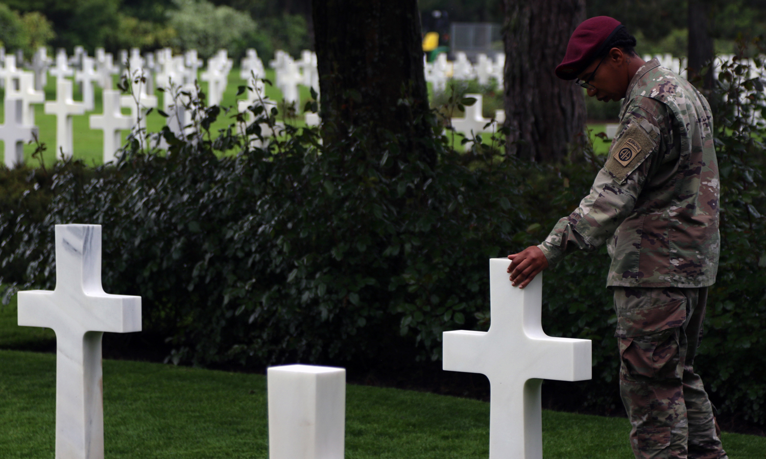Staff Sgt. Mavis Bradford, an 82nd Airborne Division choir member, spends a solemn moment at a paratroopers grave at the Normandy American Cemetery and Memorial during a staff ride on May 31, at Normandy, France. Bradford and dozens of other division paratroopers will honor the paratrooper fore fathers of the division by participating in the D-Day commemoration and ceremonies.