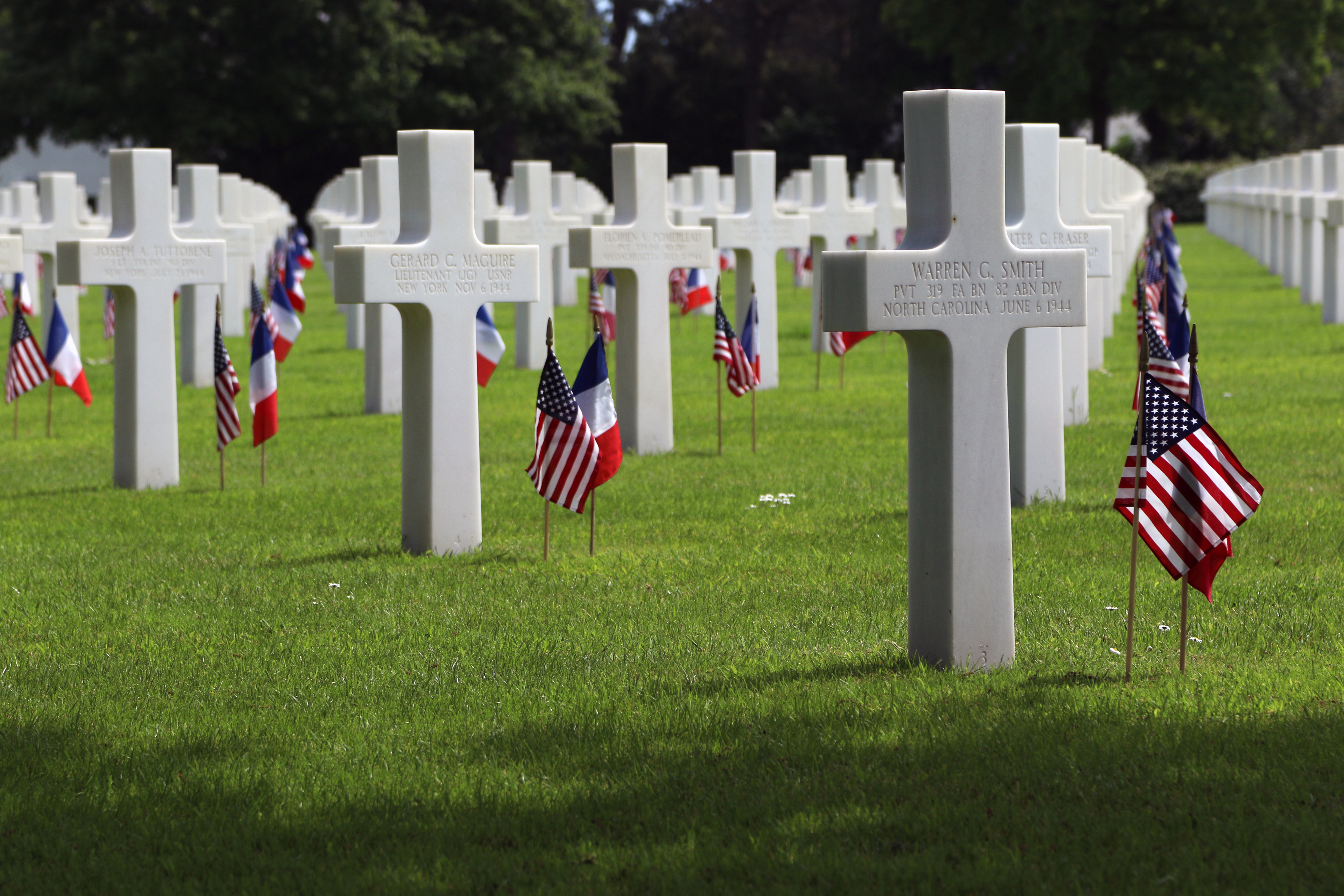 The tombstone of U.S. Army Pvt. Warren G. Smith, right, a paratrooper assigned to the 319th Field Artillery Battalion, 82nd Airborne Division, at the Normandy American Cemetery and Memorial on May 28, 2018, in Colleville-sur-Mer, France. More than 9,000 graves are dedicated to the 82nd Airborne Division paratroopers and other servicemembers who lost their lives during World War II, many of them on D-Day, June 6, 1944.  (U.S. Army photo by Sgt. 1st Class Daniel Wallace)