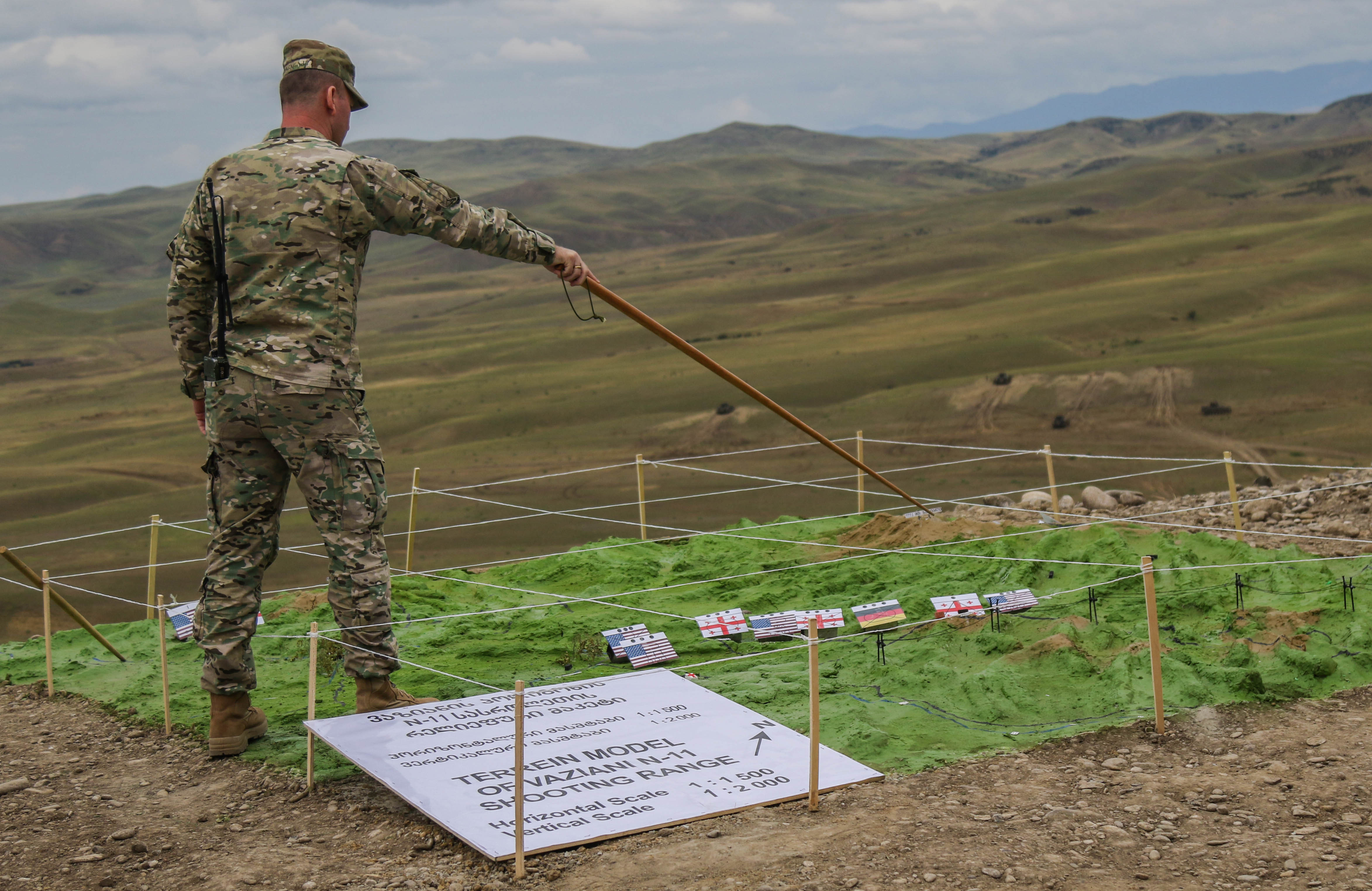 A Georgian army soldier demonstrates on a terrain model the location where mechanized fighting vehicles are shooting at Vaziani Training Area, Georgia, Aug. 15, 2018. The combined live-fire exercise was part of the culmination of Noble Partner 18, a cooperatively-led multinational training exercise in its fourth iteration which supported the training of Georgian Armed Forces' mechanized and Special Operation Forces, U.S. Regionally Aligned Forces, the U.S. Army and Air National Guard from the state of Georgia, and 11 other participating nations.