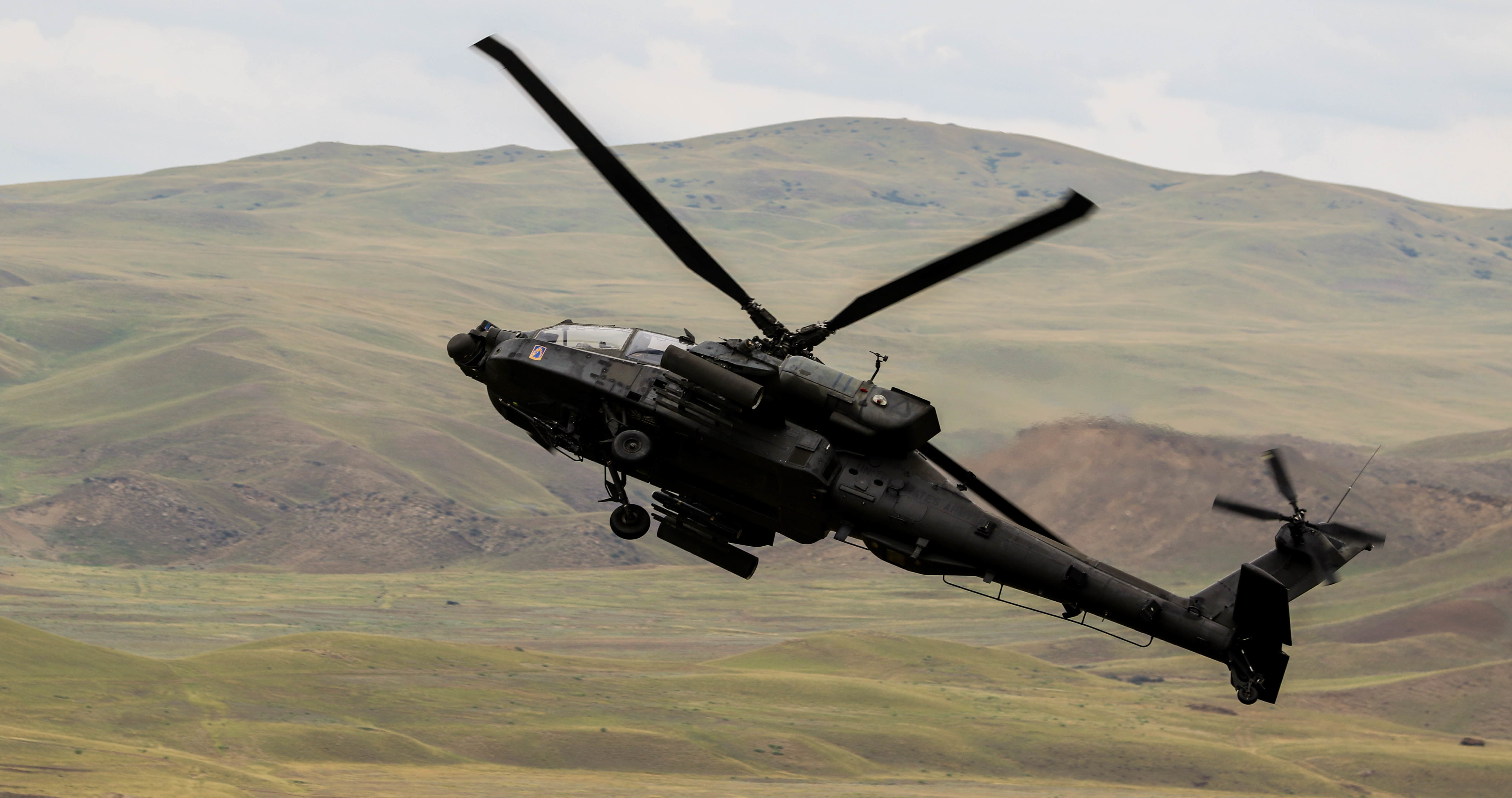 An AH-64 Apache helicopter flies over Vaziani Training Area, Georgia during combined live-fire exercise, Aug. 15, 2018. The exercise was part of the culmination of Noble Partner 18, a cooperatively-led multinational training exercise in its fourth iteration which supported the training of Georgian Armed Forces' mechanized and Special Operation Forces, U.S. Regionally Aligned Forces, the U.S. Army and Air National Guard from the state of Georgia, and 11 other participating nations. (U.S. Army photo by Sgt. Kris Bonet)