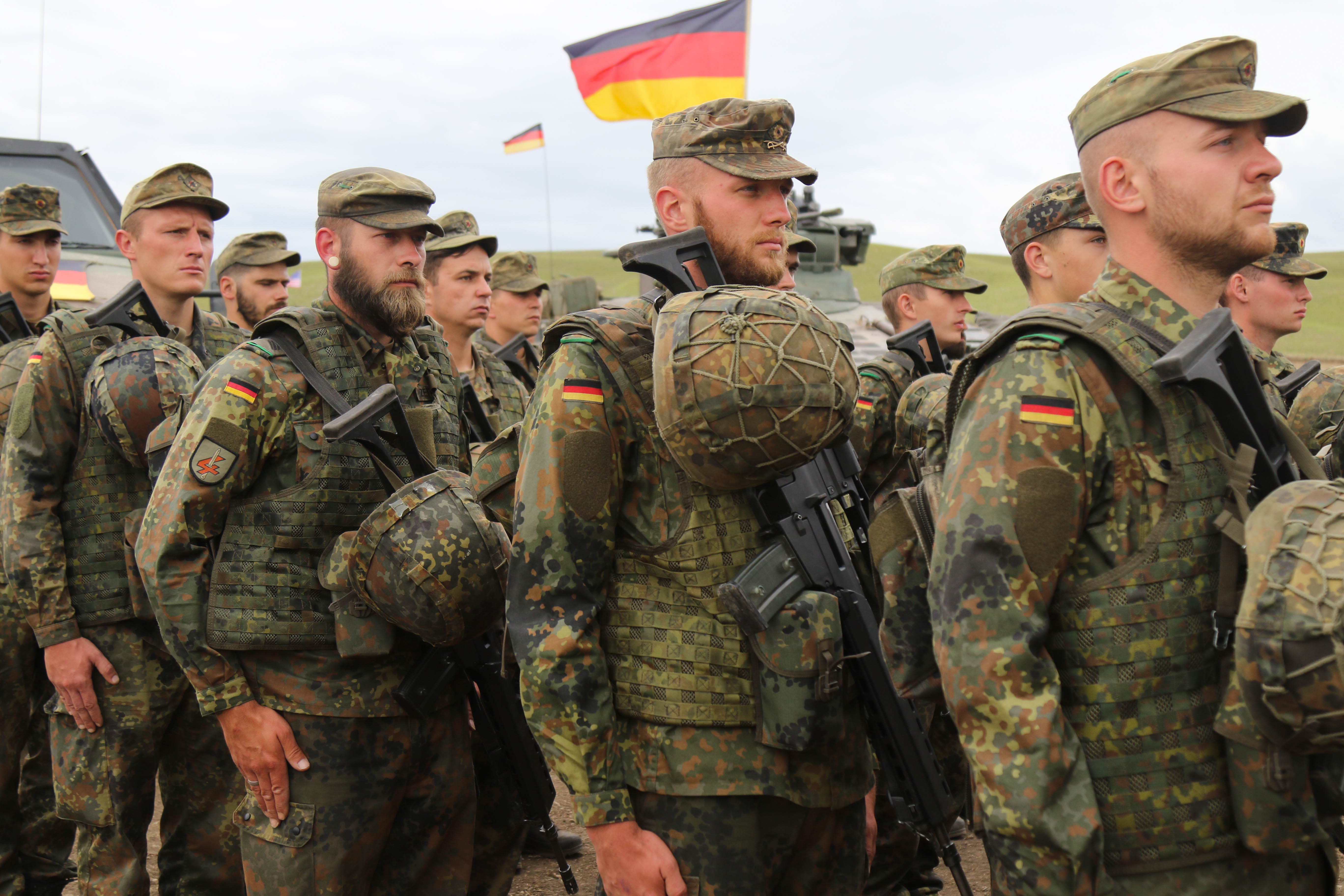 German army soldiers stand at attention for the Georgian natinal anthem during the closing ceremony for Noble Partner 18 at Vaziani Training Area, Georgia, Aug. 15, 2018. Noble Partner 18 was a cooperatively-led multinational training exercise in its fourth iteration which supported the training of Georgian Armed Forces' mechanized and Special Operation Forces, U.S. Regionally Aligned Forces, the U.S. Army and Air National Guard from the state of Georgia, and 11 other participating nations. (U.S. Army photo by Sgt. Kris Bonet)