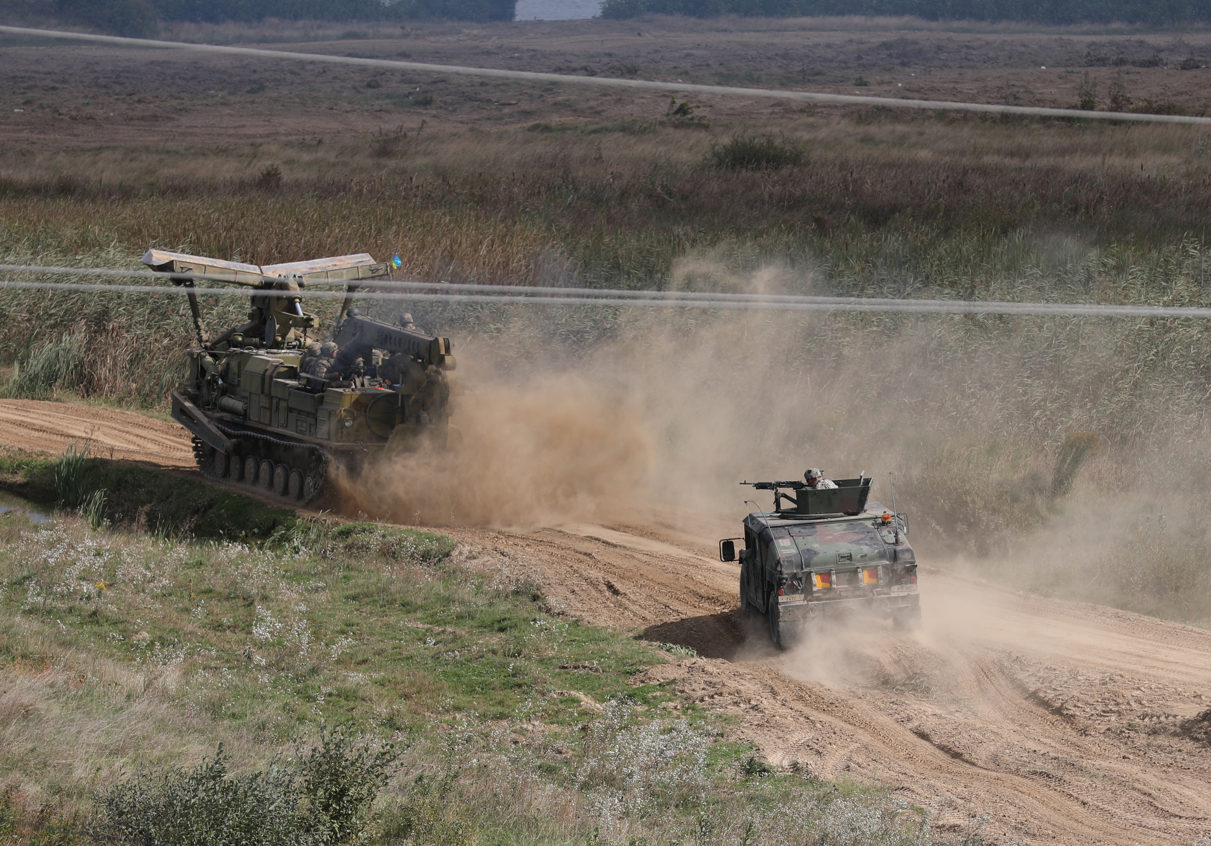 A high mobility multi-wheeled vehicle from the 101st Airborne Division (Air Assault) provides fire support for a Ukraine engineer vehicle during a water gap crossing demonstration as part of Rapid Trident 2019 in Yavoriv, Ukraine, Sept. 20, 2019. RT19 is an annual, multinational exercise occurring from Sept. 13-28, 2019, which involves approximately 3,700 personnel from 14 nations, that supports joint combined interoperability among partner militaries of Ukraine and the United States, as well as Partnership for Peace nations and NATO allies. (U.S. Army photo by Sgt. Kyle Larsen.)